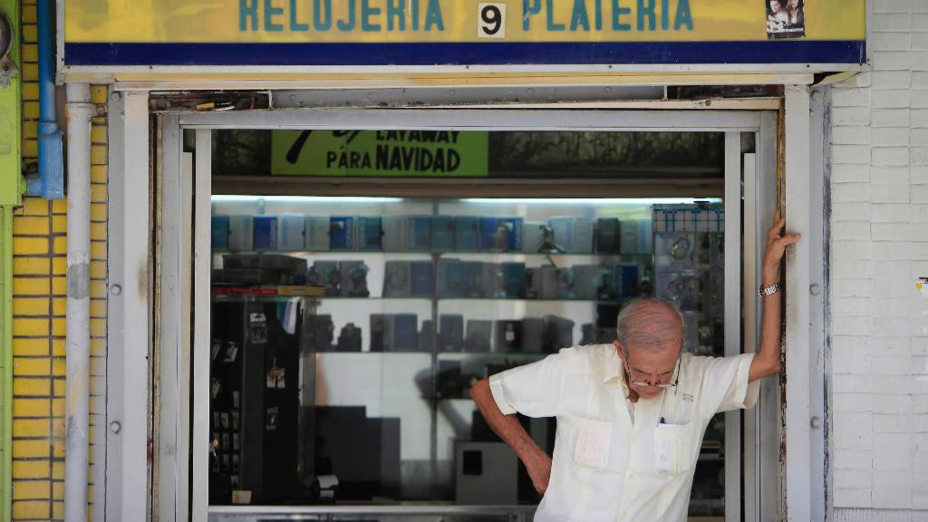 A man stands in front of a jewelry store in the neighborhood of Rio Piedras in San Juan, Puerto Rico, Monday, June 29, 2015. The jewelry itself is surrounded by closed down businesses. International economists released a critical report on Puerto Rico's economy Monday on the heels of the governor's warning that the island can't pay its $72 billion public debt. (AP Photo/Ricardo Arduengo)