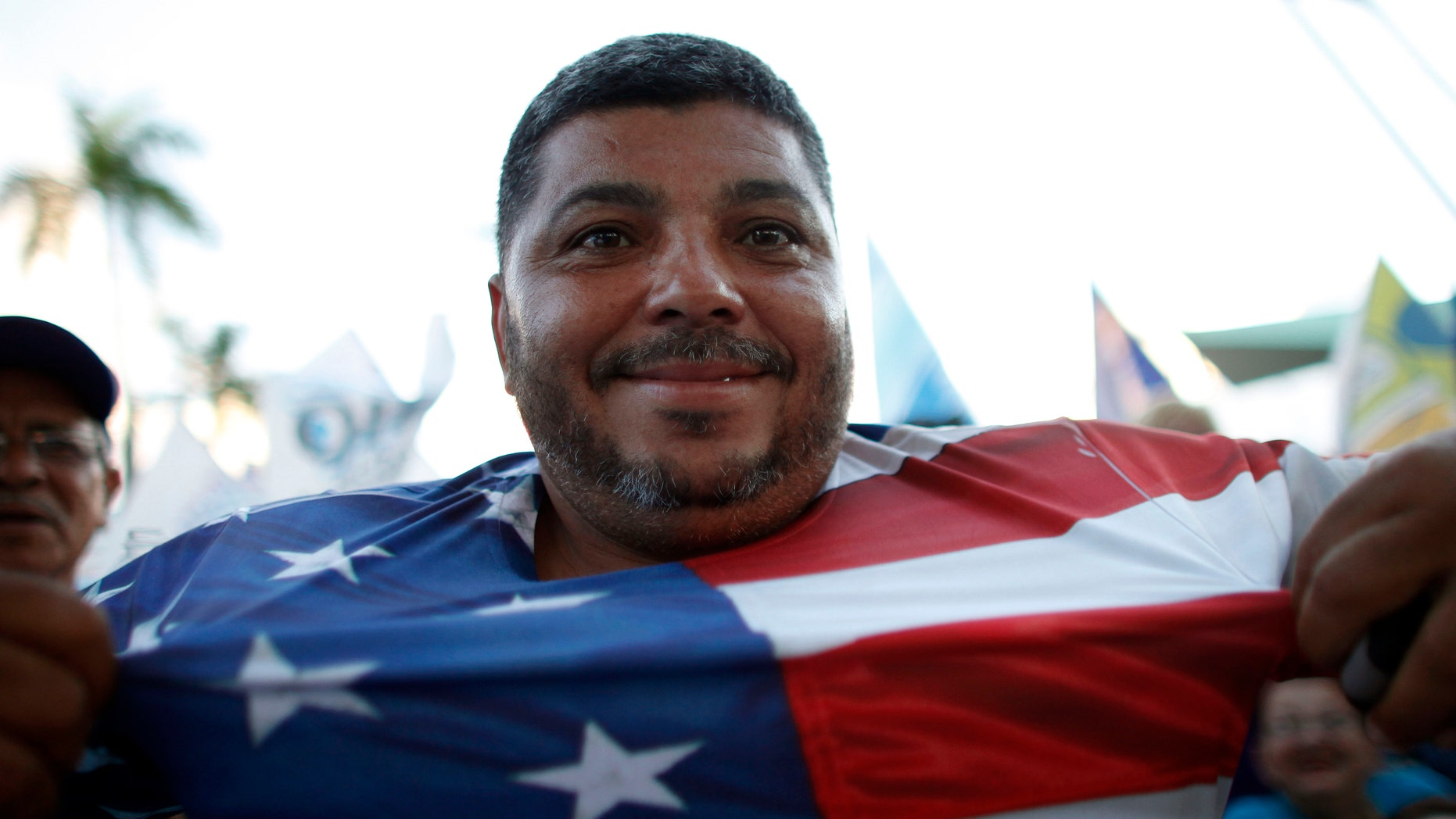 A pro-statehood New Progressive Party supporter shows his T-shirt printed with the U.S. flag at the closing campaign rally for the pro-statehood New Progressive Party in San Juan, Puerto Rico, Saturday, Nov. 3, 2012. (AP Photo/Ricardo Arduengo)