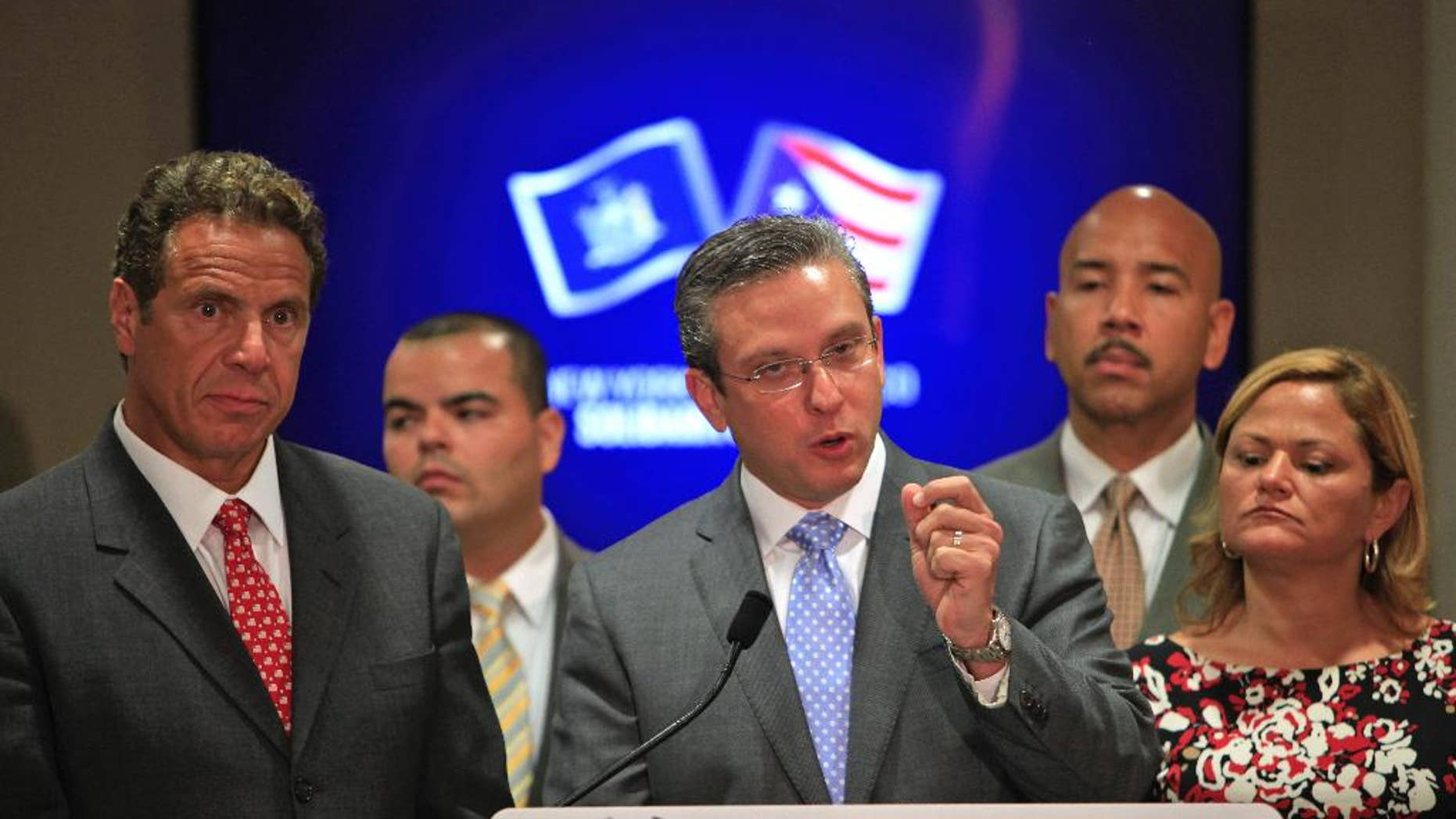 New York Gov. Andrew Cuomo, left, stands next to Puerto Rico Gov. Alejandro Garcia Padilla, during a joint news conference in San Juan, Puerto Rico, Tuesday, Sept. 8, 2015. Cuomo and a delegation of top state officials met with Puerto Rico's Gov. Alejandro Garcia Padilla, pictured left, on Tuesday to develop what he called a historic partnership with the U.S. territory to help it emerge from a deepening economic crisis. (AP Photo/Ricardo Arduengo)
