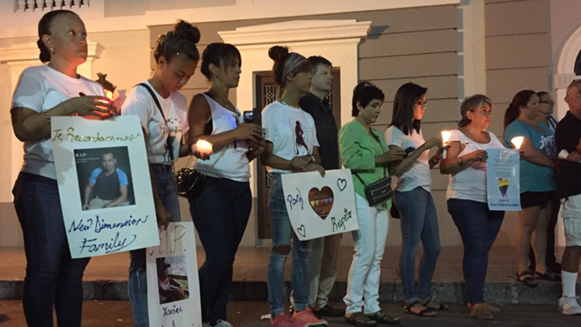 People gather with posters and candles in Ponce, Puerto Rico, Monday, June 13, 2016, during a vigil for the victims of Sunday's Orlando shootings at a gay nightclub in Florida. At least 5 of the 49 victims were from Ponce, the second largest city on Puerto Rico's southern coast. (AP Photo/Danica Coto)