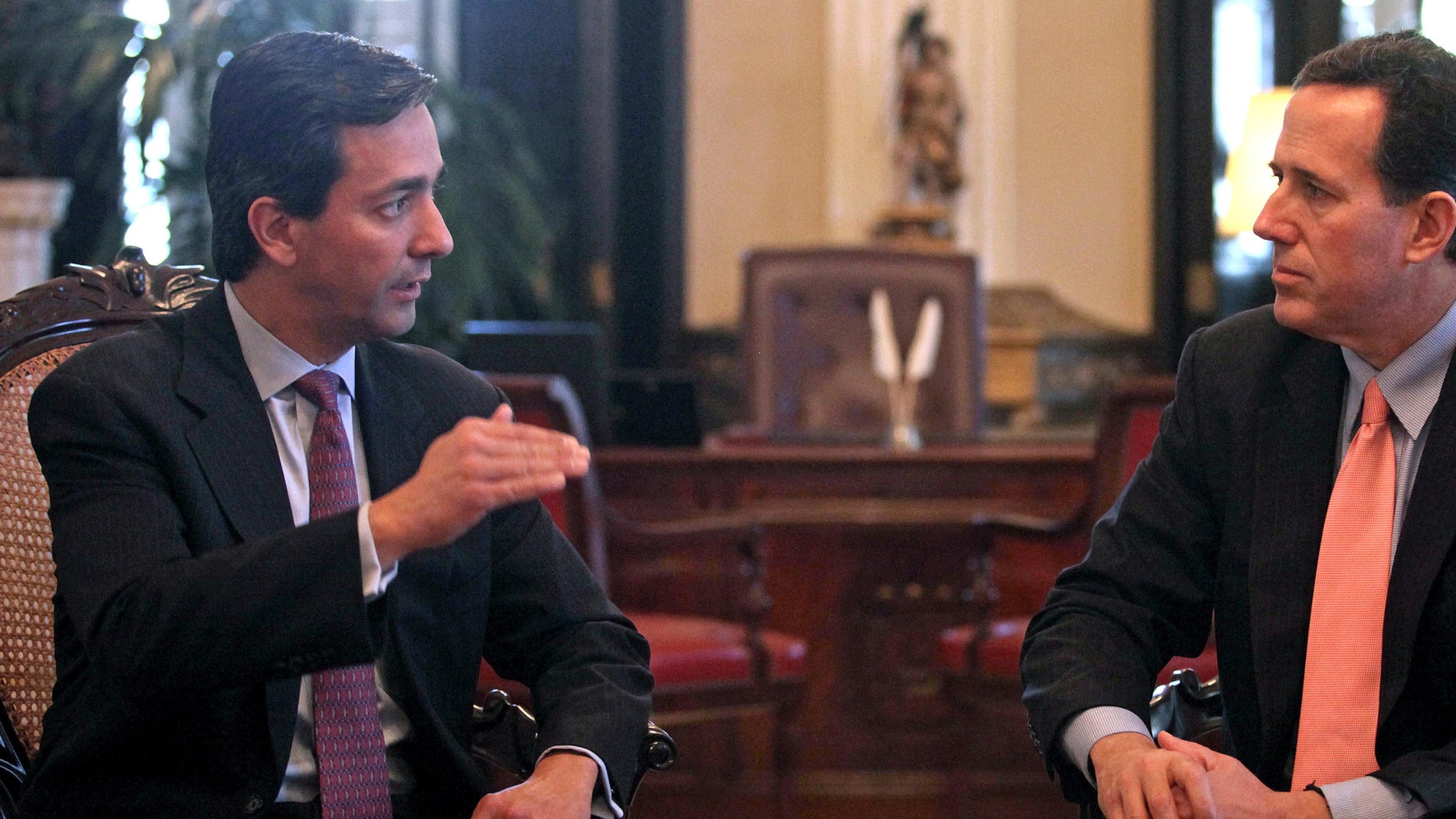 Commonwealth of Puerto Rico Governor Luis Fortuno, left, talks to Republican presidential candidate, former Pennsylvania Sen. Rick Santorum during their meeting at the governor's mansion La Fortaleza, or Fortess, in San Juan, Puerto Rico, Wednesday March 14, 2012. (AP Photo/Dennis M. Rivera Pichardo)