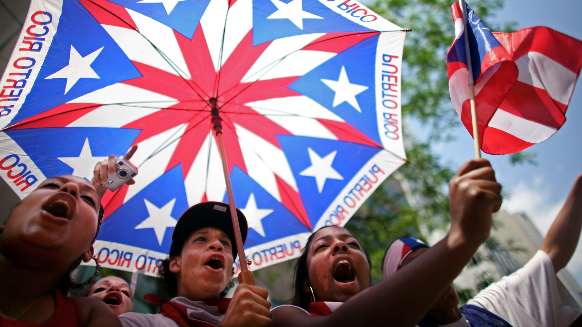 NEW YORK CITY - JUNE 8:   (L-R) Stephanie Morales, Christian Ortiz and Simone Sonii cheer at the annual Puerto Rico Day Parade June 8, 2008 in New York City. The parade honoring Puerto Ricans is an annual New York City tradition and takes place along Fifth Avenue.  (Photo by Yana Paskova/Getty Images)