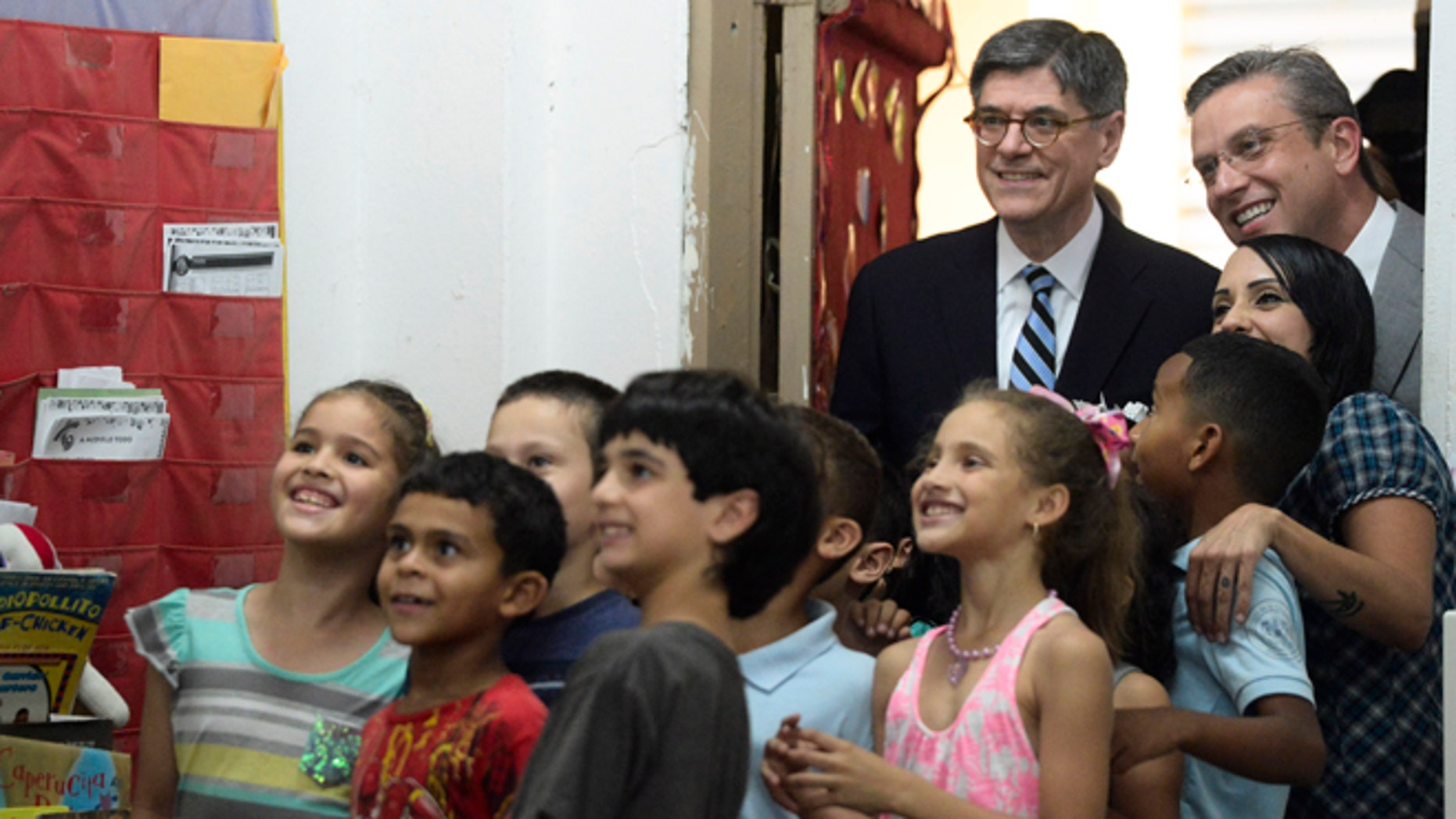 U.S. Treasury Secretary Jacob Lew, top, second from right, poses for photos with students as he takes a classroom tour with Puerto Rico Governor Alejandro Garcia Padilla, top right, at the Eleanor Roosevelt Elementary School in San Juan, Puerto Rico, Monday, May 9, 2016. Lew hoped to jump-start congressional efforts to aid debt-stricken Puerto Rico, traveling to the U.S. territory on Monday and focusing on basic services in jeopardy at public hospitals and schools. (AP Photo/Carlos Giusti)