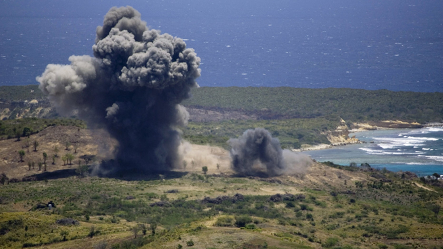 FILE - In this April 17, 2008 file photo, unexploded ordinance is blown up in a controlled demolition at the former U.S. Naval Training Range on Vieques island, Puerto Rico. A U.S. Agency has issued a long-awaited report saying it did not find any proof that decades of military activity in the Puerto Rican island of Vieques sickened residents who blame the federal government for high rates of cancer, asthma and other illnesses. (AP Photo/Brennan Linsley, File)
