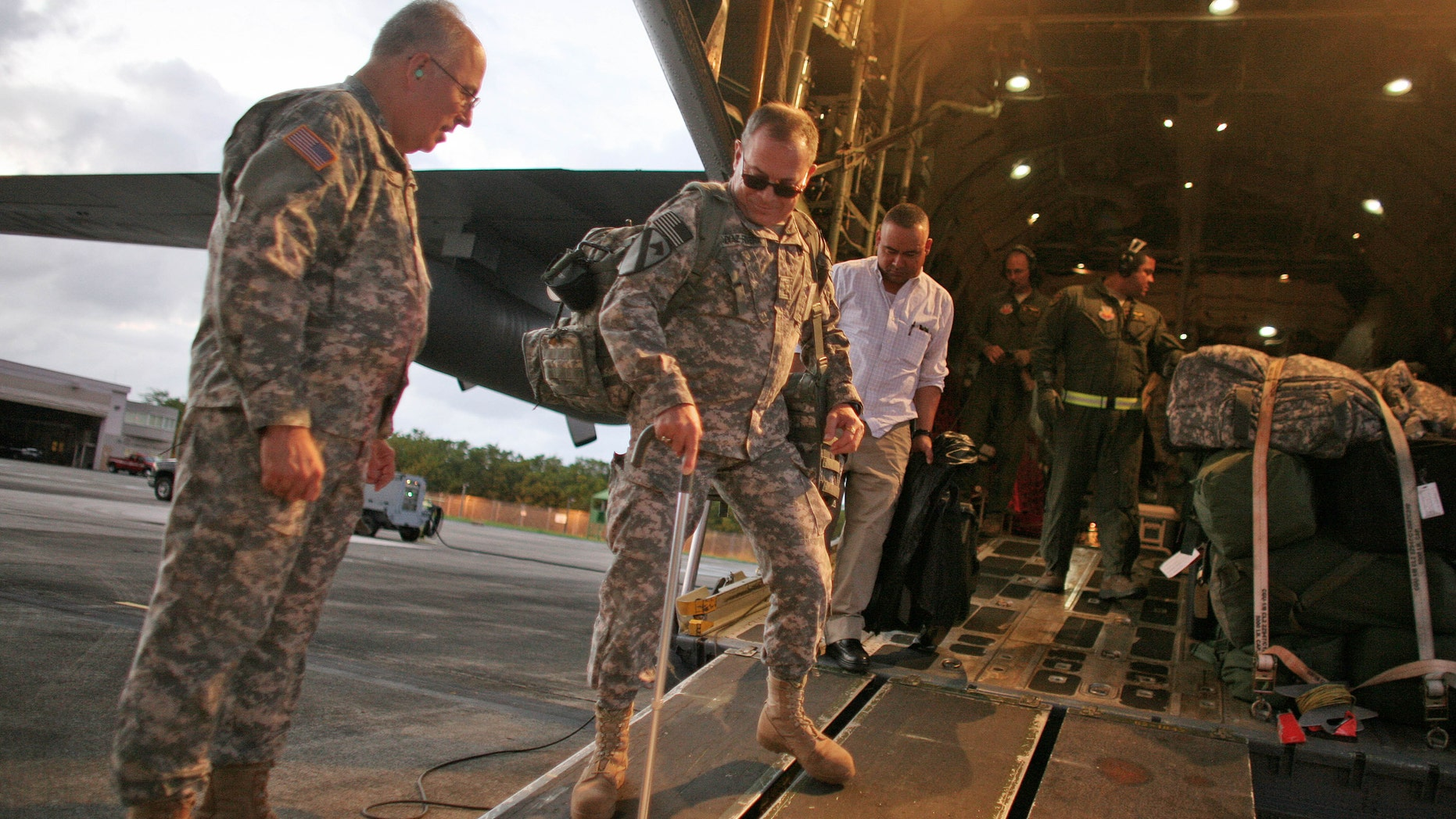 U.S. Army Chief Warrant Officer Diaz-Rivera, center, arrives to San Juan, Puerto Rico, Tuesday, Dec. 20, 2011. Puerto Rico National Guard officials say they flew home some 20 soldiers for a short break from their medical treatment. Maj. Gen. Antonio Vicens says some time at home with their families will help them recover from wounds sustained in Afghanistan, Iraq and elsewhere. (AP Photo/Ricardo Arduengo)
