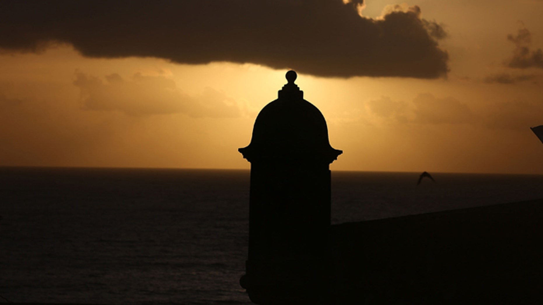 SAN JUAN, PUERTO RICO - JUNE 30:  The sun rises near a guard tower at Fort San Felipe del Morro a day after Puerto Rican Governor Alejandro Garcia Padilla gave a speech regarding the government's $72 billion debt on June 30, 2015 in San Juan, Puerto Rico.  The Governor said in his speech that the people will have to sacrifice and share in the responsibilities for pulling the island out of debt.  (Photo by Joe Raedle/Getty Images)
