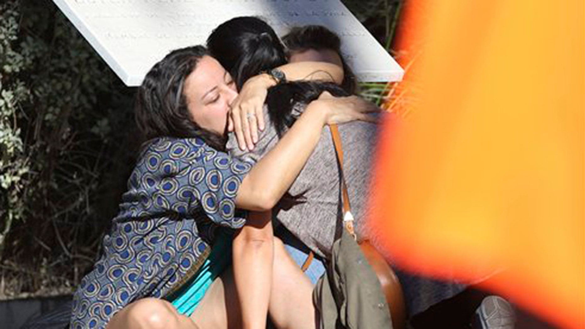 Parents of victims embrace each other near the scene of a truck attack in Nice, Friday, July 15, 2016.