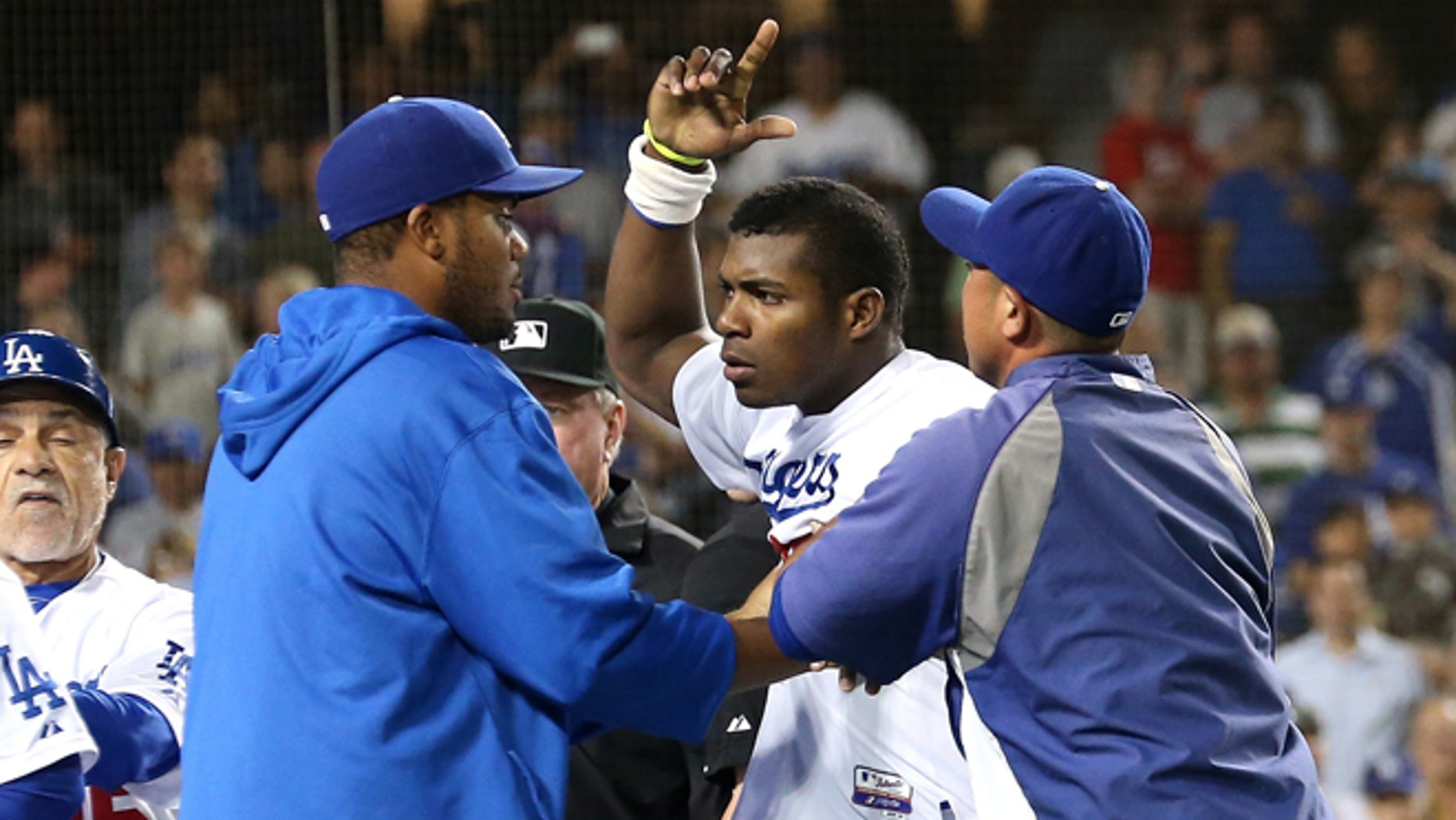 LOS ANGELES, CA - JUNE 11:  Yasiel Puig #66 of the Los Angeles Dodgers is restrained by teammates during a benches clearing brawl after Zack Greinke was hit by a pitch in the seventh inning against the Arizona Diamondbacks at Dodger Stadium on June 11, 2013 in Los Angeles, California.  Puig had been hit earlier in the game.  (Photo by Stephen Dunn/Getty Images)
