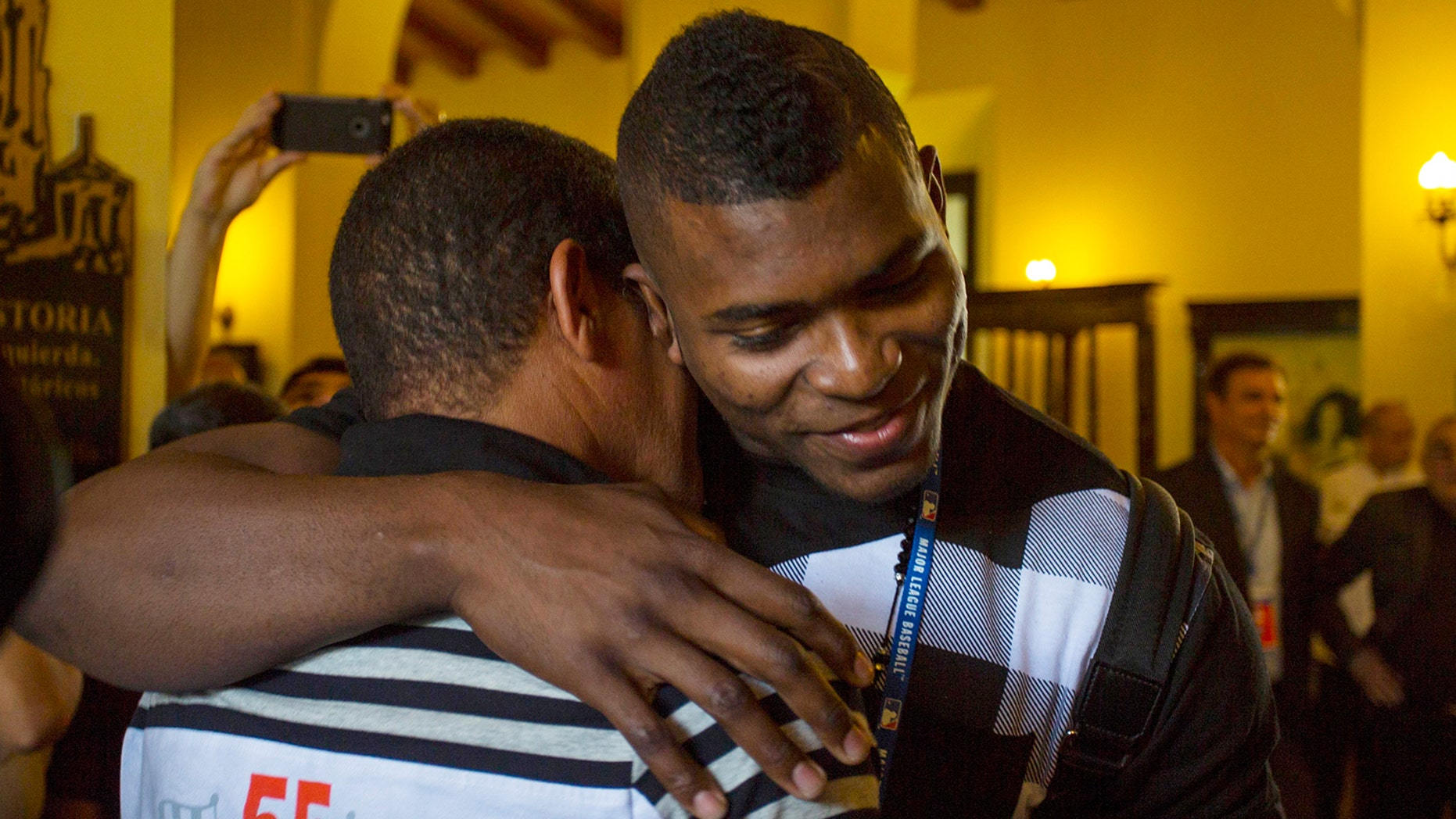 "Los Angeles Dodgers outfielder Yasiel Puig, right, hugs his former coach Juan Arechavaleta as he arrives to Hotel Nacional in Havana, Cuba, Tuesday, Dec. 15, 2015. A lineup of Cuban baseball superstars including some of the most famous defectors in recent memory made a triumphant return Tuesday as part of the first Major League Baseball trip to the island since 1999. ""I'm very happy to be here,"" said Puig, who had been barred from returning to Cuba until he was granted special permission for this week's trip. (AP Photo/Desmond Boylan)"