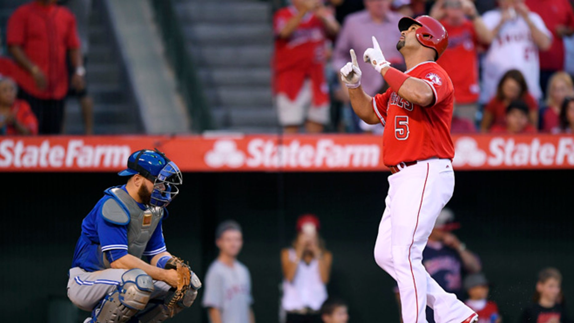 Los Angeles Angels' Albert Pujols, right, points to the sky as he scores after hitting a solo home run as Toronto Blue Jays catcher Russell Martin kneels at the plate during the second inning of a baseball game, Saturday, Sept. 17, 2016, in Anaheim, Calif. (AP Photo/Mark J. Terrill)