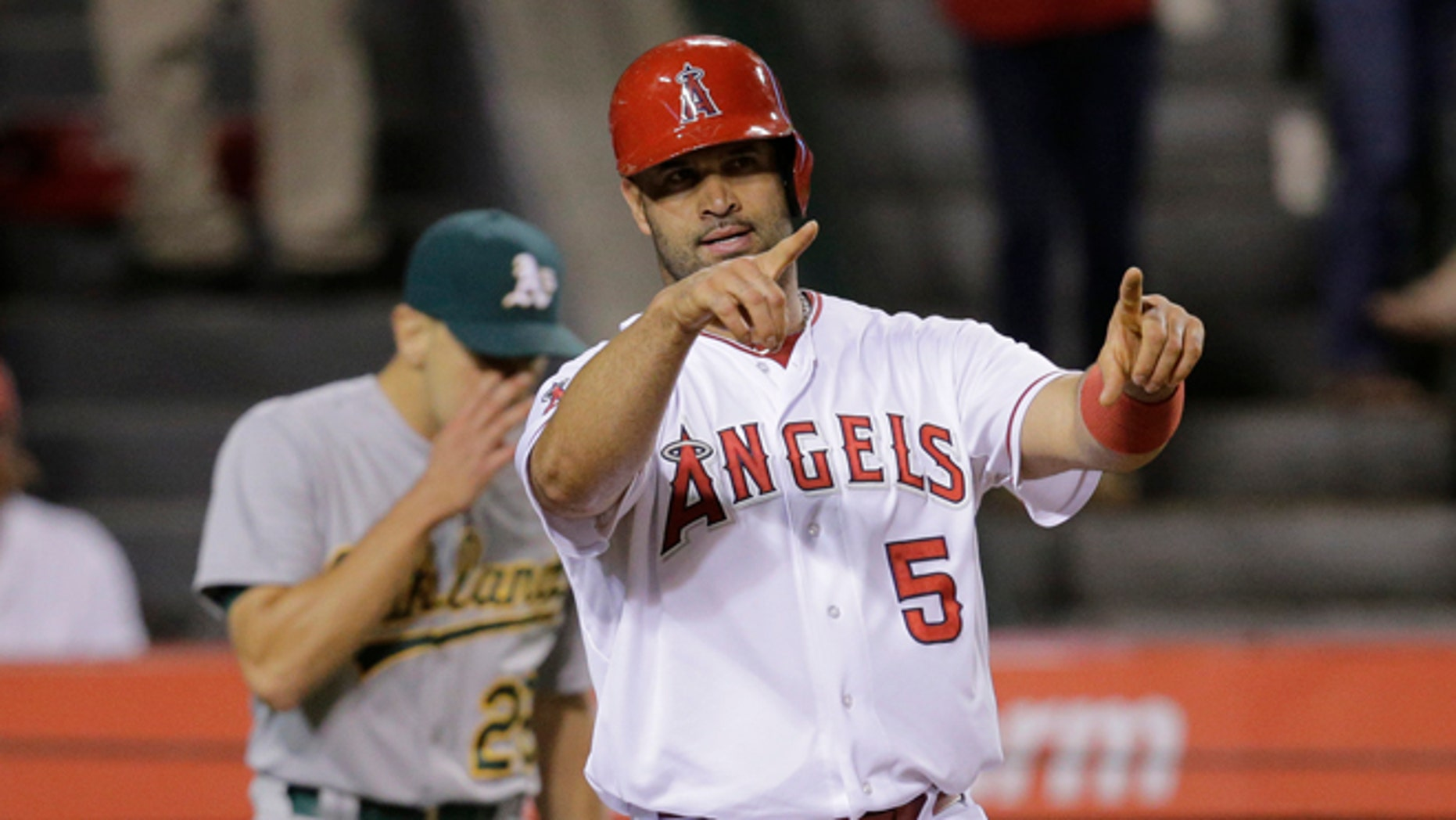 Los Angeles Angels' Albert Pujols points to teammate David Freese after he scored on a single hit by Freese during the fifth inning of a baseball game against the Oakland Athletics, Tuesday, Sept. 29, 2015, in Anaheim, Calif. (AP Photo/Jae C. Hong)