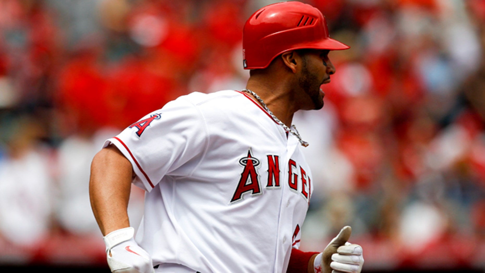 Los Angeles Angels' Albert Pujols reacts after flying out against the Baltimore Orioles during the first inning of a baseball game in Anaheim, Calif., Sunday, April 22, 2012. (AP Photo/Chris Carlson)