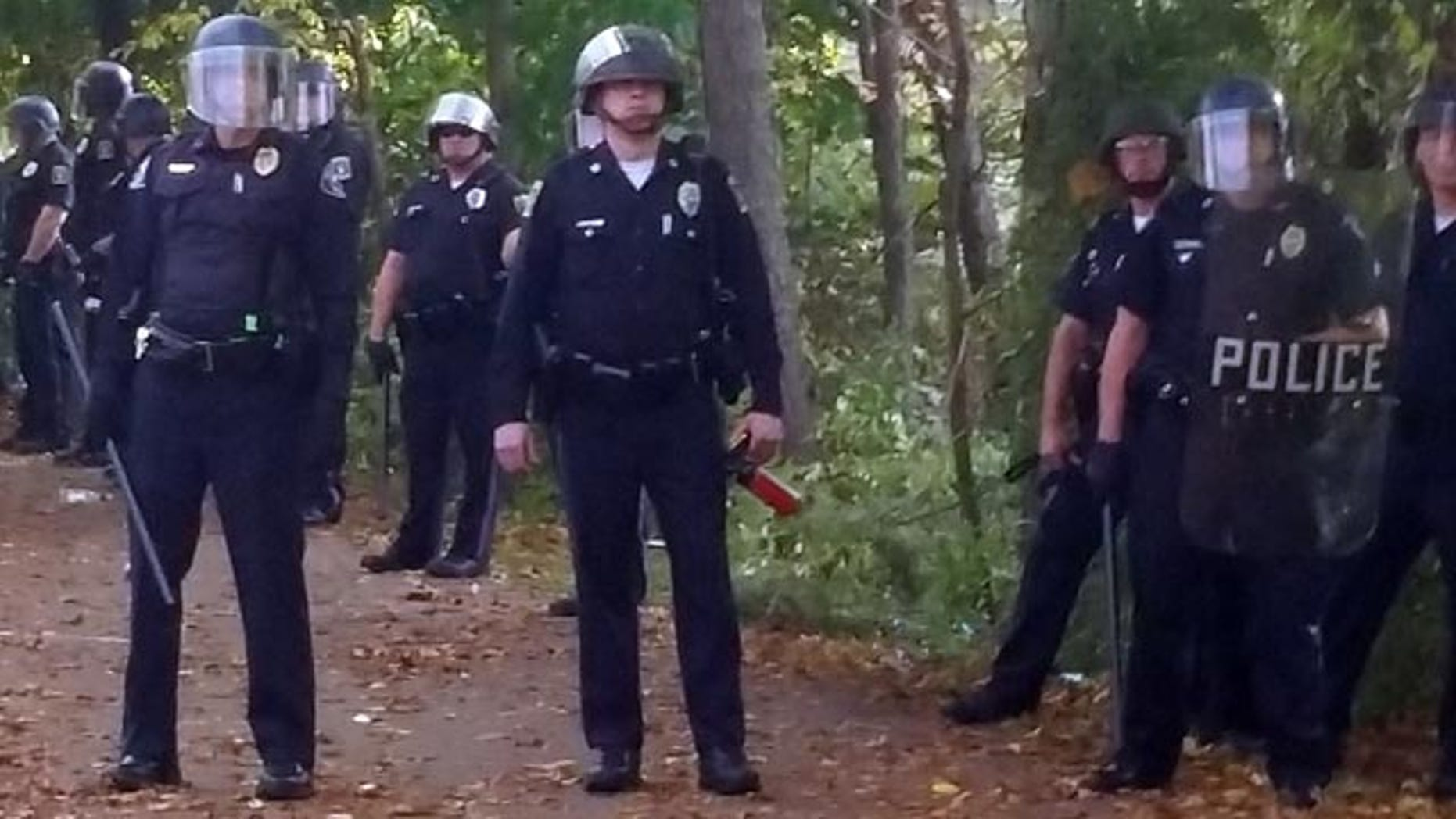 October 18, 2014: In this photo provided by Seth Meyer, police officers line up. Local police, firefighters and ambulances in Keene, New Hampshire responded to large crowds of students at the annual Pumpkin Festival near Keene State College.(AP Photo/Seth Meyer)
