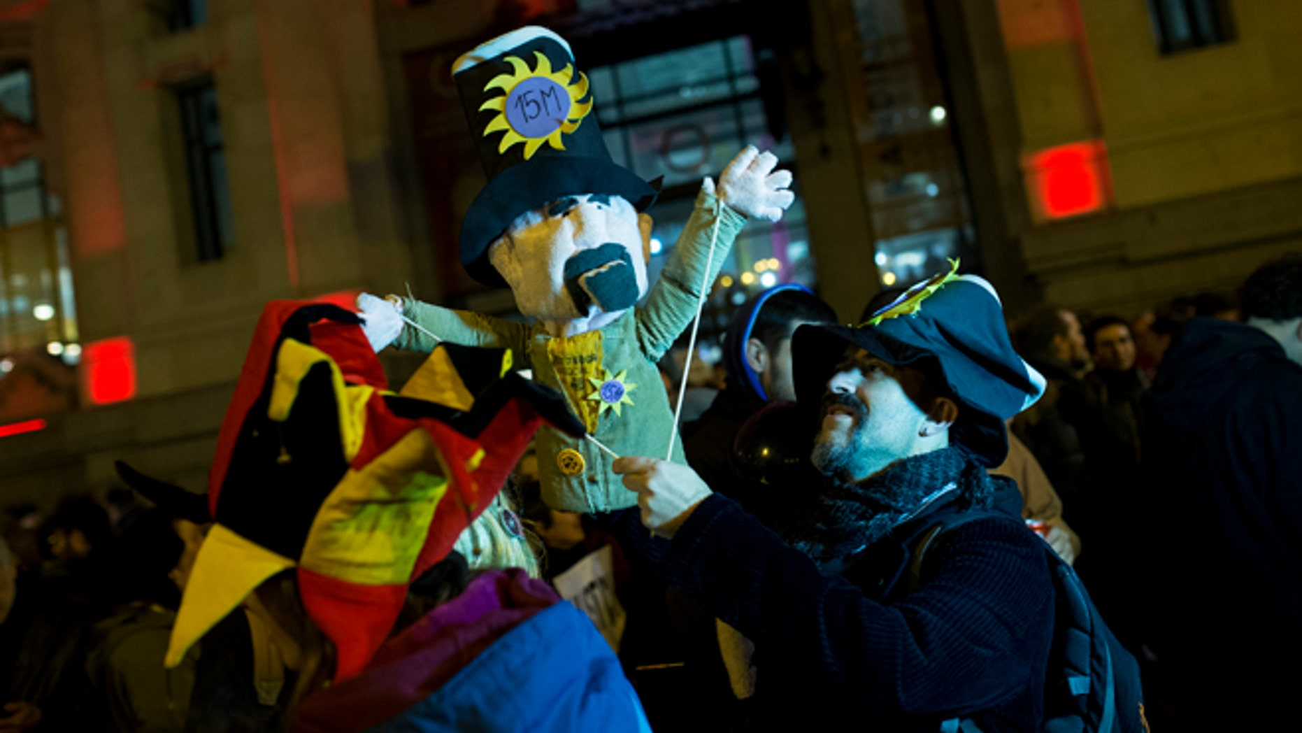 "A man, holding a puppet, gathers with others outside Madrid city hall in support of two puppeteers who were detained without a bail last Friday for using a sign saying, ""Long Live Alka ETA,"" in a word-play reference to Spain's armed Basque group ETA and al-Qaida, in Madrid, Wednesday, Feb. 10, 2016. A Spanish court on Wednesday ordered the release of two puppeteers jailed since last week for allegedly praising terrorism in a controversial Carnival show funded with public money. (AP Photo/Francisco Seco)"