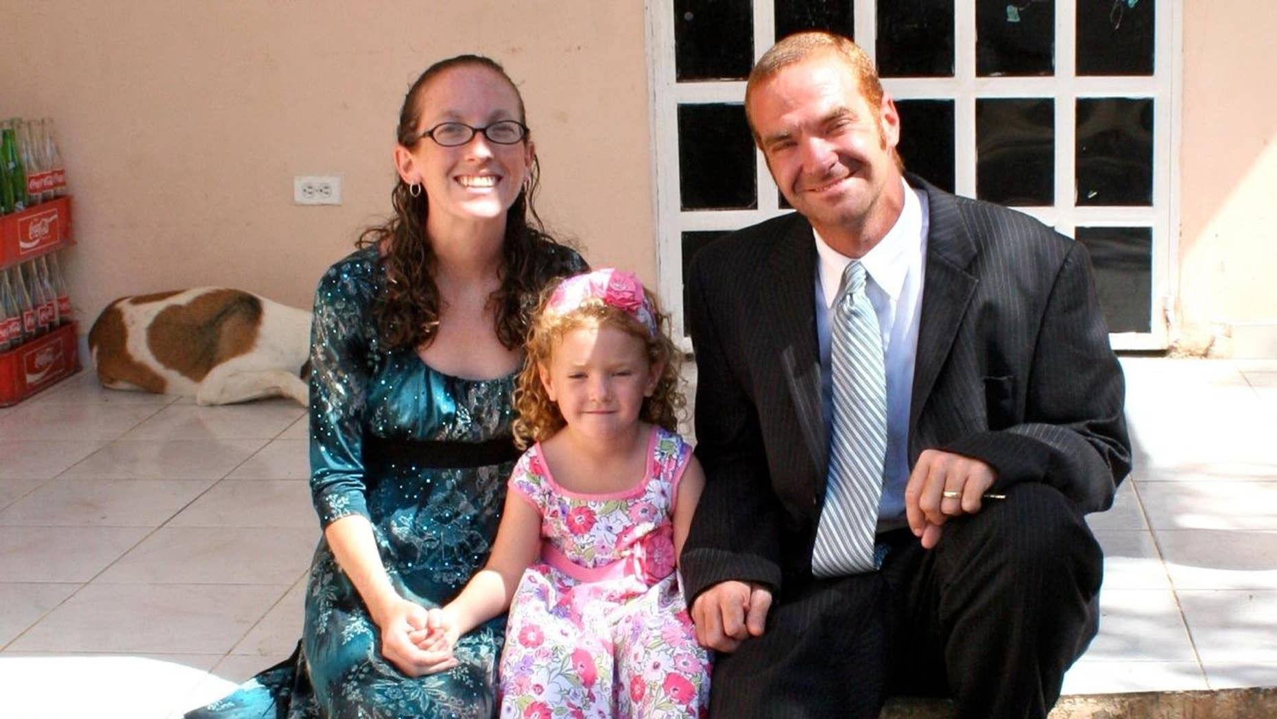 Leann and Daniel Pye sit with their 4-year-old daughter Riann in front of their orphanage in Jacmel, Haiti.