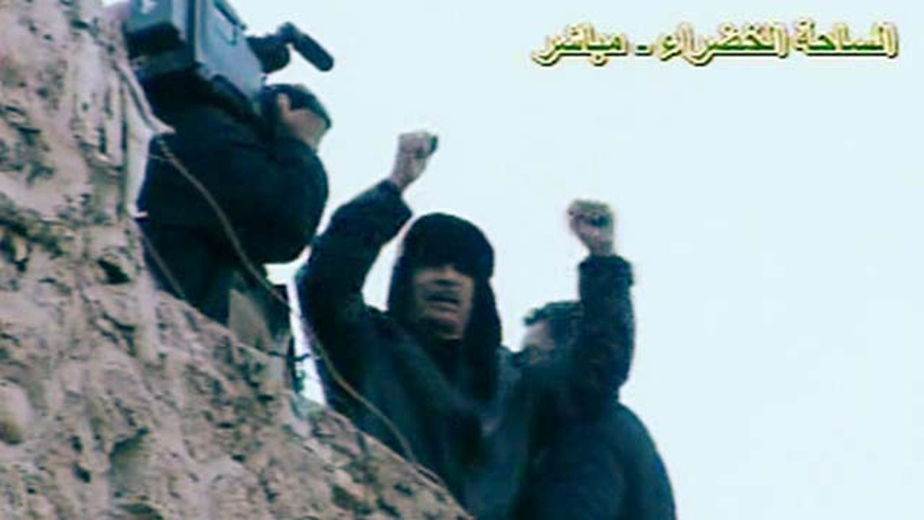 In this Feb. 25, 2011 file image made from Libya State Television, Libyan leader Moammar Gadhafi speaks to followers from the top of a stone wall in The Green Square, Tripoli, Libya. Even after rebels stormed into the capital and overwhelmed his residence, Libya's Moammar Gadhafi has plenty of places to hide. The man who ruled Libya for 42 years is known to have deep bunkers under his Bab al-Aziziya compound in Tripoli, which rebel fighters seized Tuesday, Aug. 23, 2011.