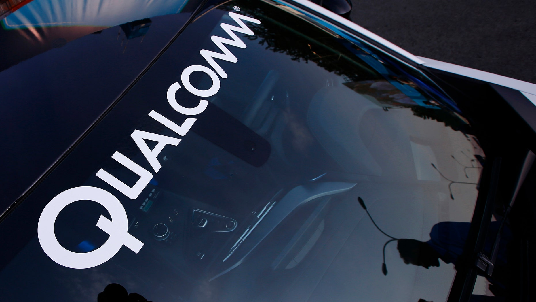 """A logo of U.S. chipmaker Qualcomm is seen on the windshield of a car in Beijing September 13, 2014. China's National Development and Reform Commission (NDRC) has investigated dozens of foreign firms over alleged """"anti-competitive behaviour"""" - from auto parts makers and milk powder producers to drugs firms and tech companies, including Qualcomm Inc,  which faces a potential record fine of more than $1 billion. From interviews with more than two dozen attorneys, executives, and experts, who have been drawn into investigations with the NDRC's price supervision and anti-monopoly bureau, a picture emerges of a culture of intimidation. The agency's aggressive tactics coincide with an increasingly sobering business climate for foreign firms in China. Fears over the ruling Communist Party's support for domestic firms has prompted some to declare the end of a golden age for foreign business in the world's second-largest economy.  To match Insight CHINA-ANTITRUST/NDRC     Picture taken September 13, 2014. REUTERS/Petar Kujundzic (CHINA - Tags: POLITICS BUSINESS LOGO CRIME LAW) - RTR46CHJ"""
