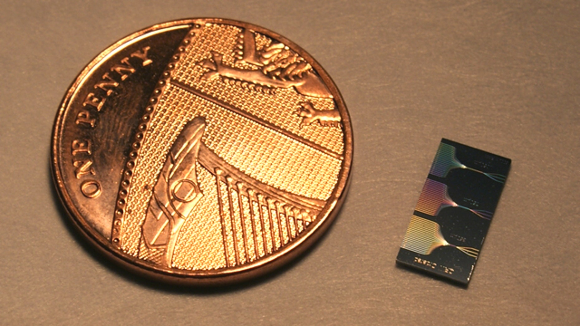 This is the photonic chip next to a UK penny. The chip contains micrometer and sub-micrometer features and guide light using a network of waveguides. The output of this network can be seen on the surface of the chip.