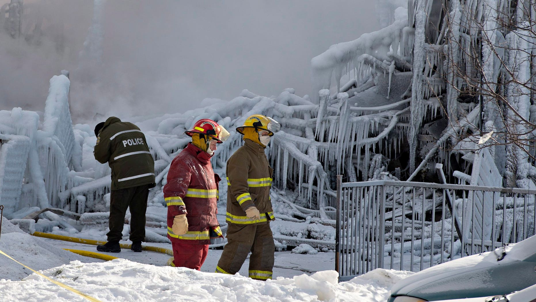 Jan. 23, 2014 - Police and firefighters survey the damage after a fatal fire at a seniors residence in L'Isle-Verte, Quebec. The fire raged through the seniors residence, killing at least 5 people and leaving about 30 unaccounted for.