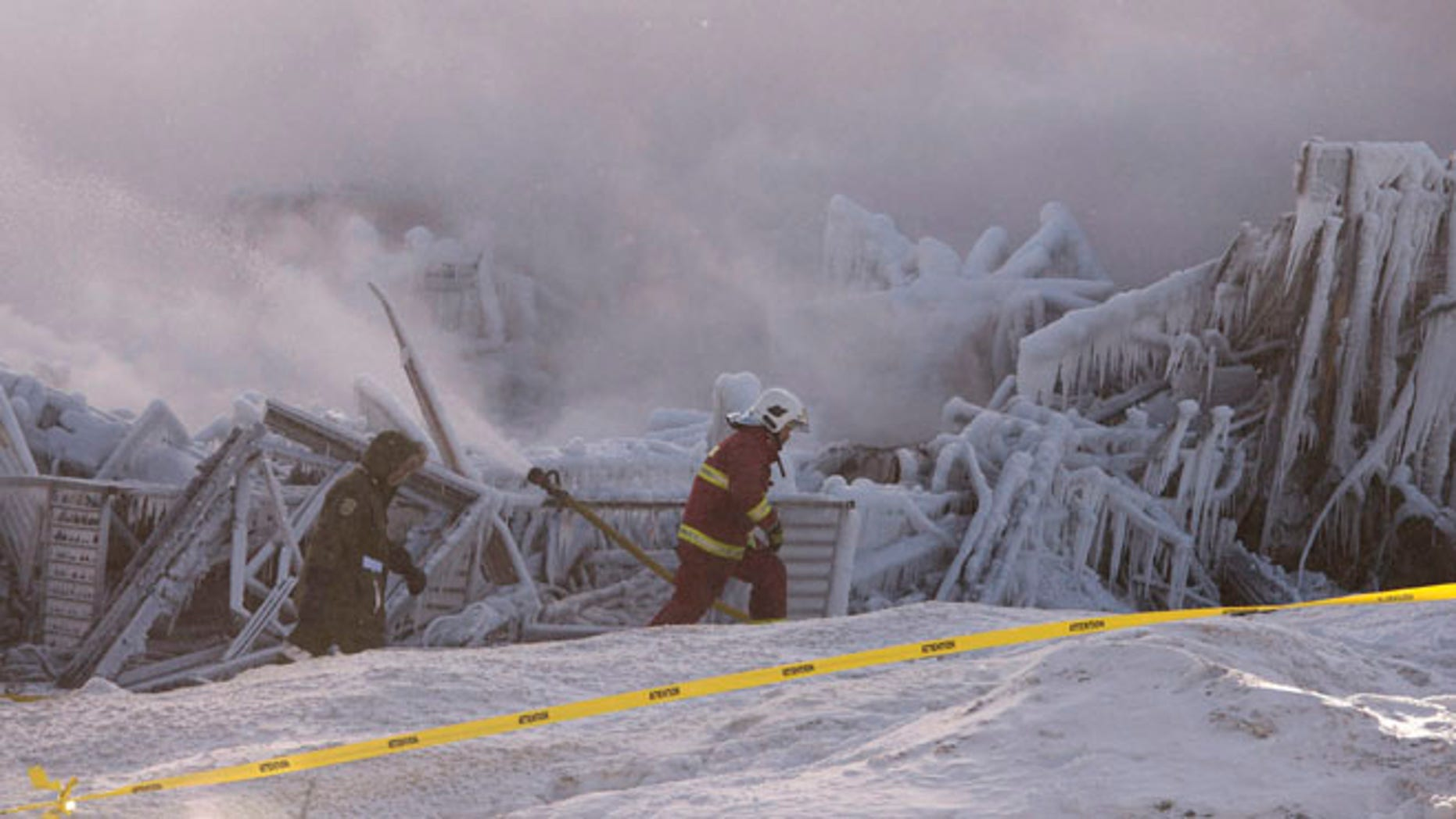 Jan. 23, 2014: Firefighters work at the scene of a senior's residence fire in L'Isle-Verte, Quebec.