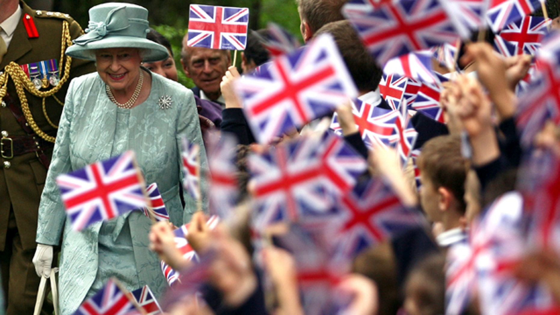 In this May 16, 2008, file photo, Britain's Queen Elizabeth II, left, is welcomed by children waving Britain's flag, upon her arrival at the British Embassy in Ankara, Turkey. Encouraged by the largely successful peace process in Northern Ireland, the queen will become the first British monarch to set foot in the Republic of Ireland on Tuesday, May 17, 2011.