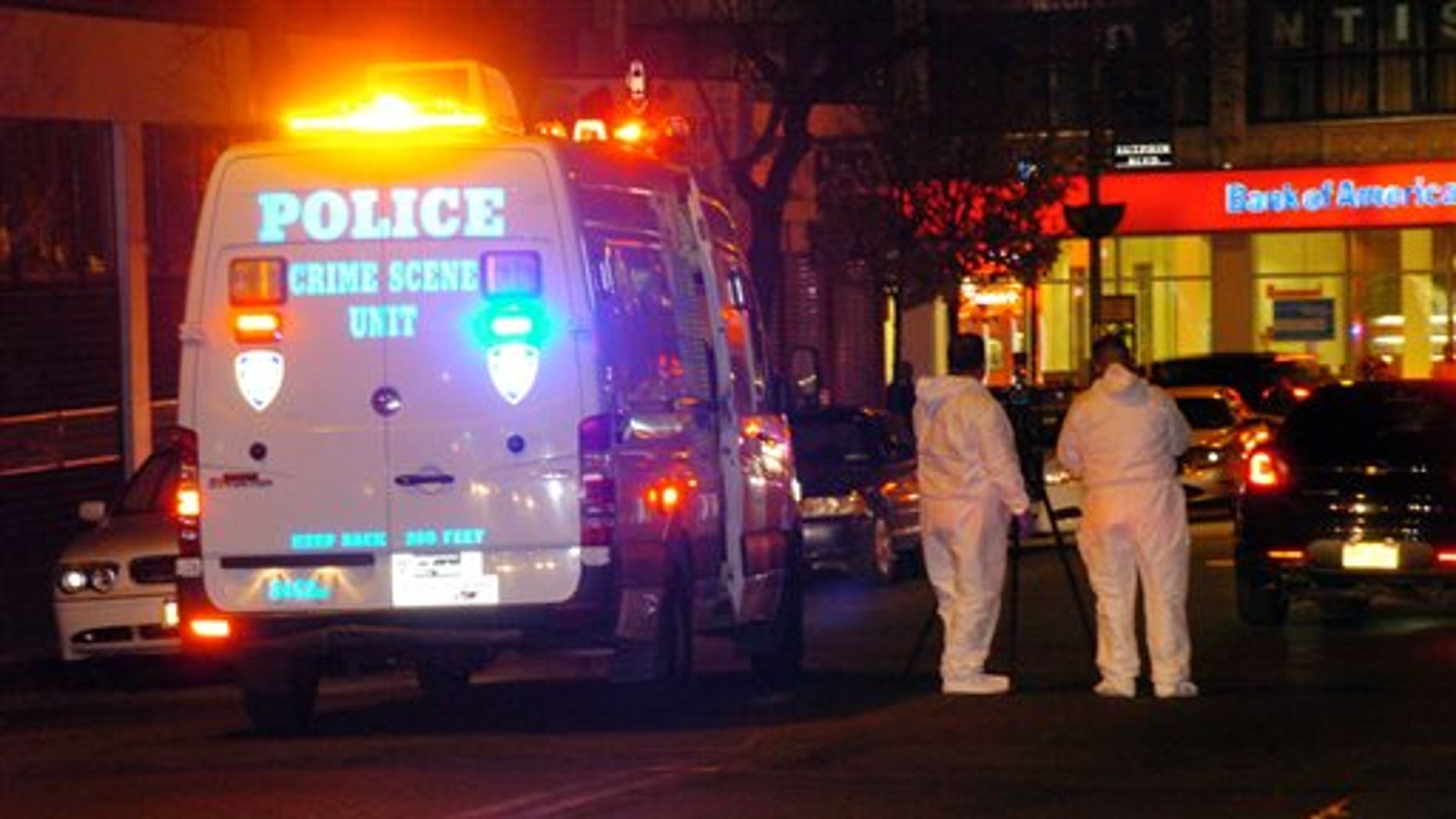 Police are investigating the deaths of a woman and two toddlers in the Queens borough of New York, Sunday, Jan. 19, 2014. Police say the bodies of a 1-year-old child, a 3-year-old child and a 21-year-old female were found in an apartment on Sutphin Blvd. in the Jamaica section of the borough. (AP Photo/David Torres)
