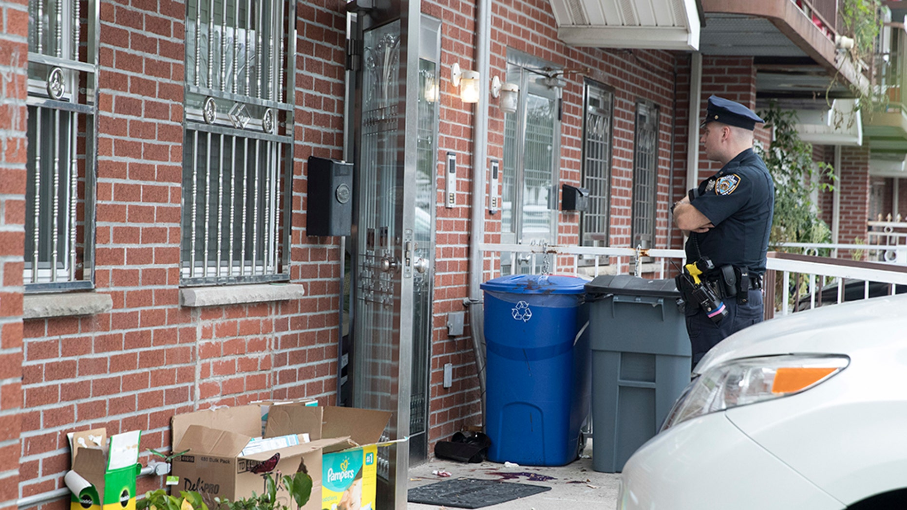 A police officer stands guard at the house were five people were stabbed overnight, Friday, Sept. 21, 2018, in New York.