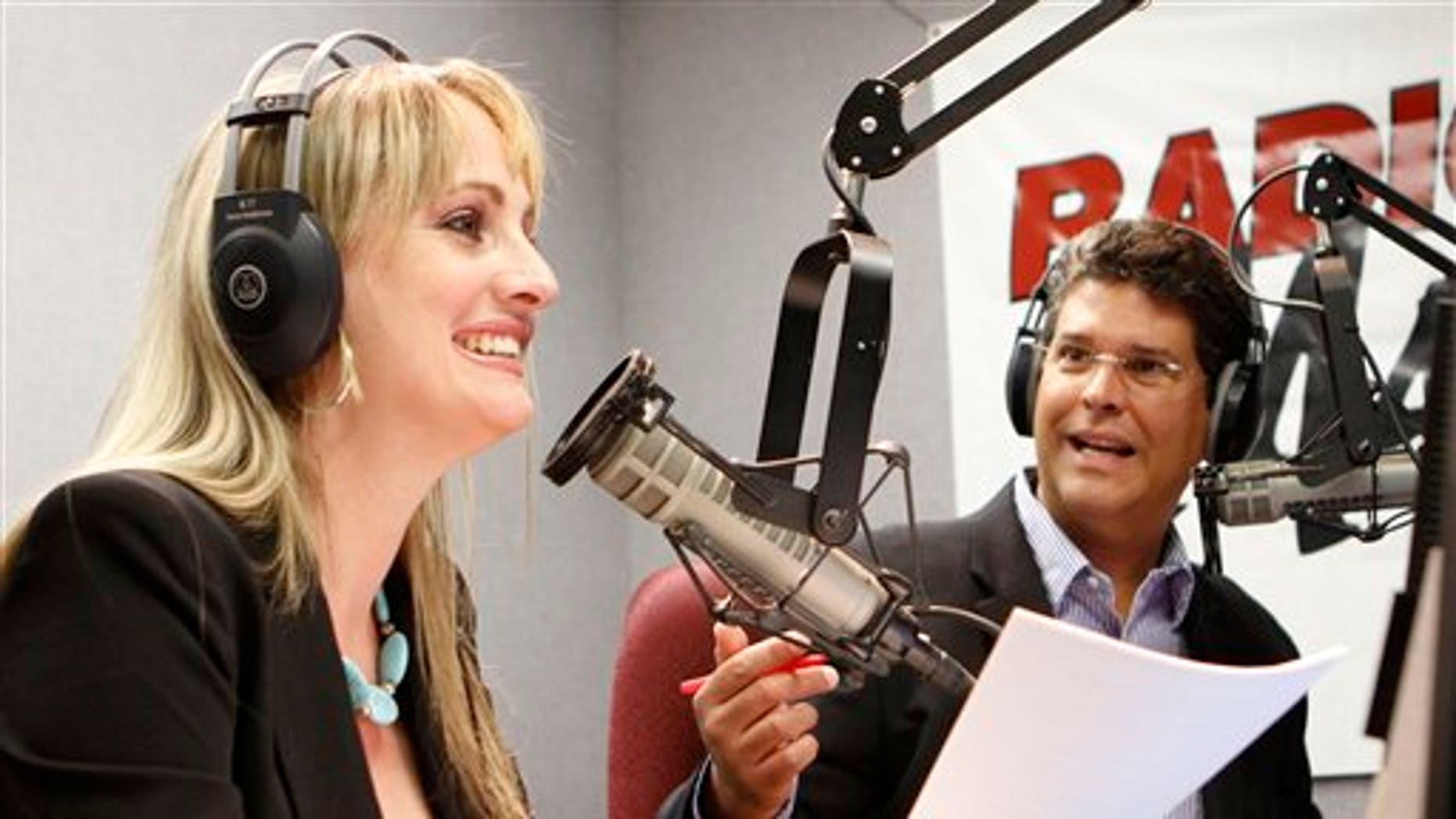 In this April 21, 2011 photo, Radio Marti's El Revoltillo, Spanish for The Scramble hosts Karen Caballero, left, and Alfredo Jacomino laugh during their radio show in Miami. A new radio show  features Caballero and Jacomino, exchanging Regis & Kelly-like banter while reading off items and services for sale from a Cuban website. The program is more practical than political since few on the island have computer access. Based on nothing more than a Cuban-style Craigslist, it seems to work, mixing useful information with humor. (AP Photo/Alan Diaz)