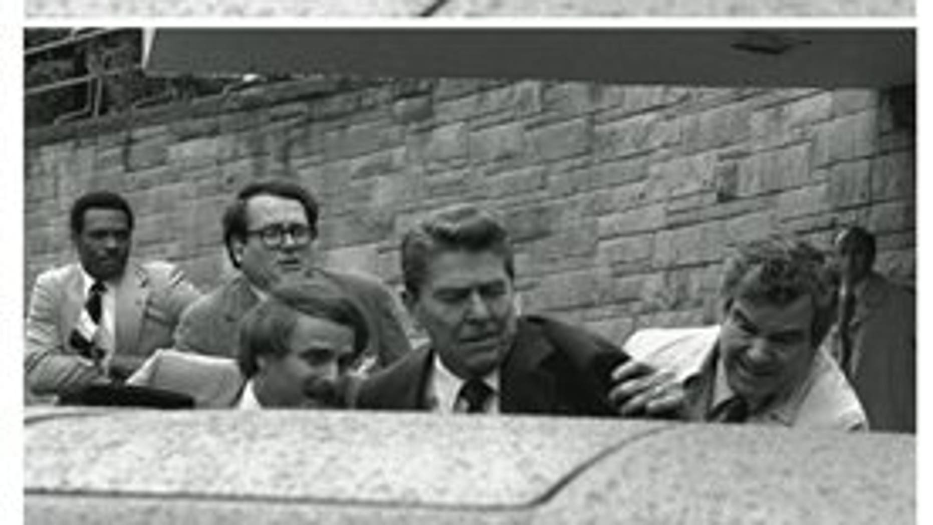 In this March 30, 1981, black-and-white three picture combo file photo, President Reagan waves, then looks up before being shoved into Presidential limousine by Secret Service agents after being shot outside a hotel in Washington. (AP Photo/Ron Edmonds, File)