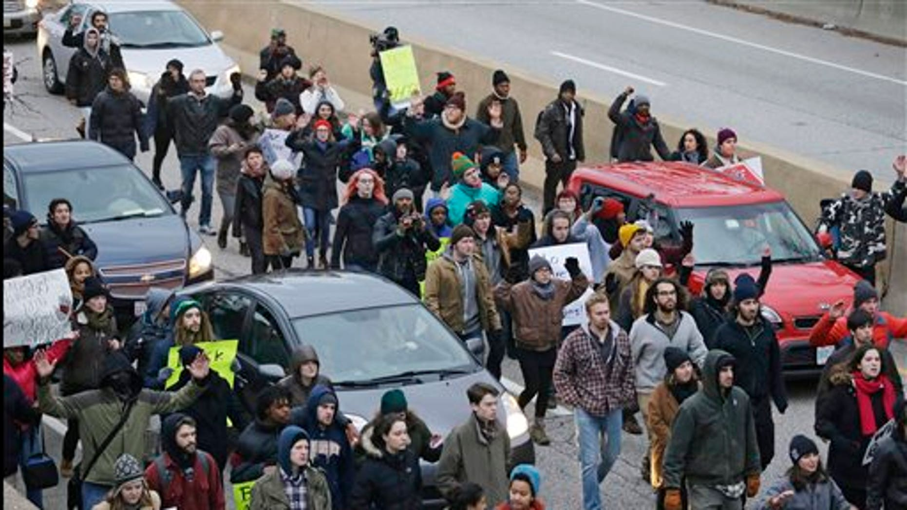 In this Nov. 25, 2014, photo, protesters block cars on the freeway during a protest over the police shooting of Tamir Rice in Cleveland. (AP Photo/Tony Dejak, File)