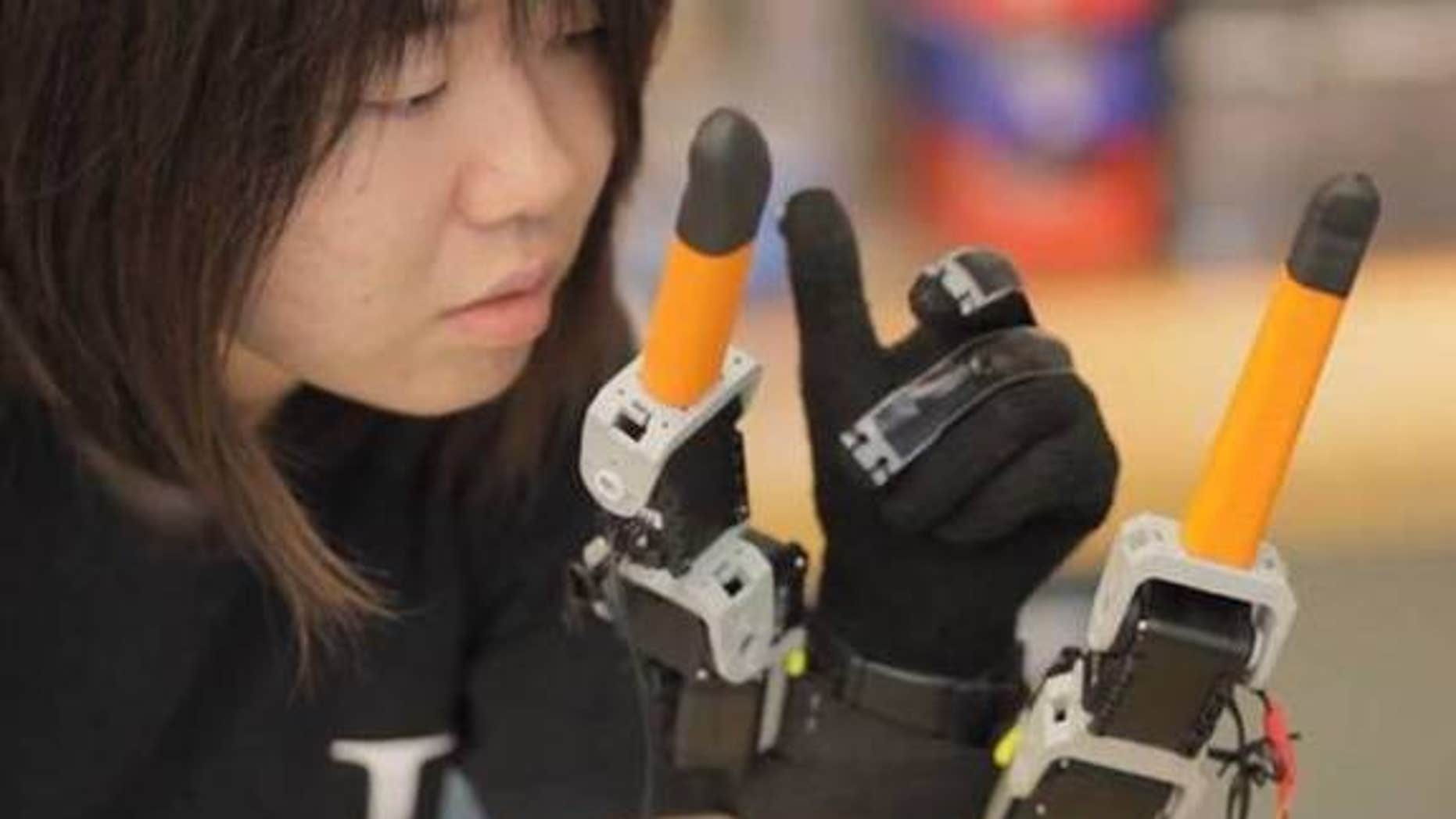MIT graduate student, Faye Wu, demonstrates the new robotic device.
