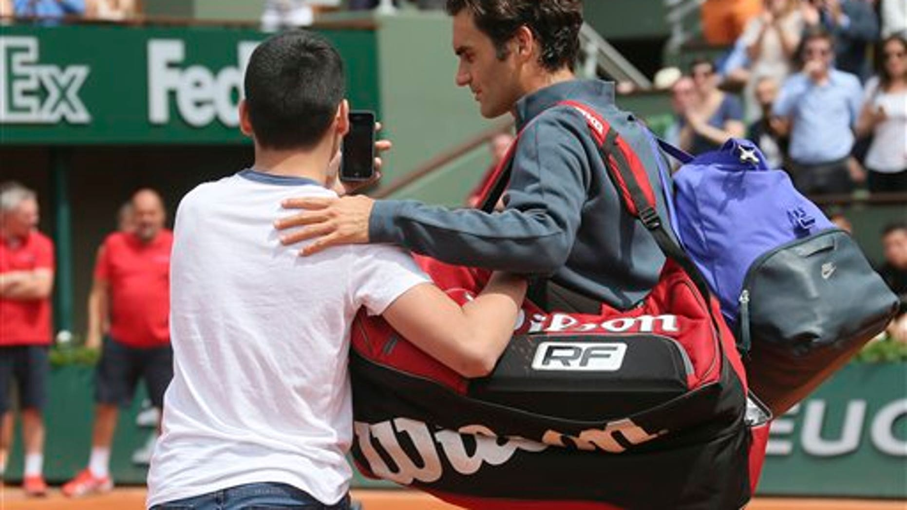 A boy who climbed down from the stands takes a selfie with Switzerland's Roger Federer in the first round match of the French Open tennis tournament in Paris, France, Sunday, May 24, 2015. (AP Photo/David Vincent)