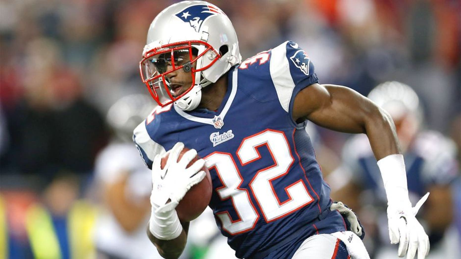 Jan 20, 2013; Foxboro, Massachusetts, USA; New England Patriots cornerback Devin McCourty (32) carries the ball during the fourth quarter against the Baltimore Ravens at Gillette Stadium. Mandatory Credit: Greg M. Cooper-USA TODAY Sports