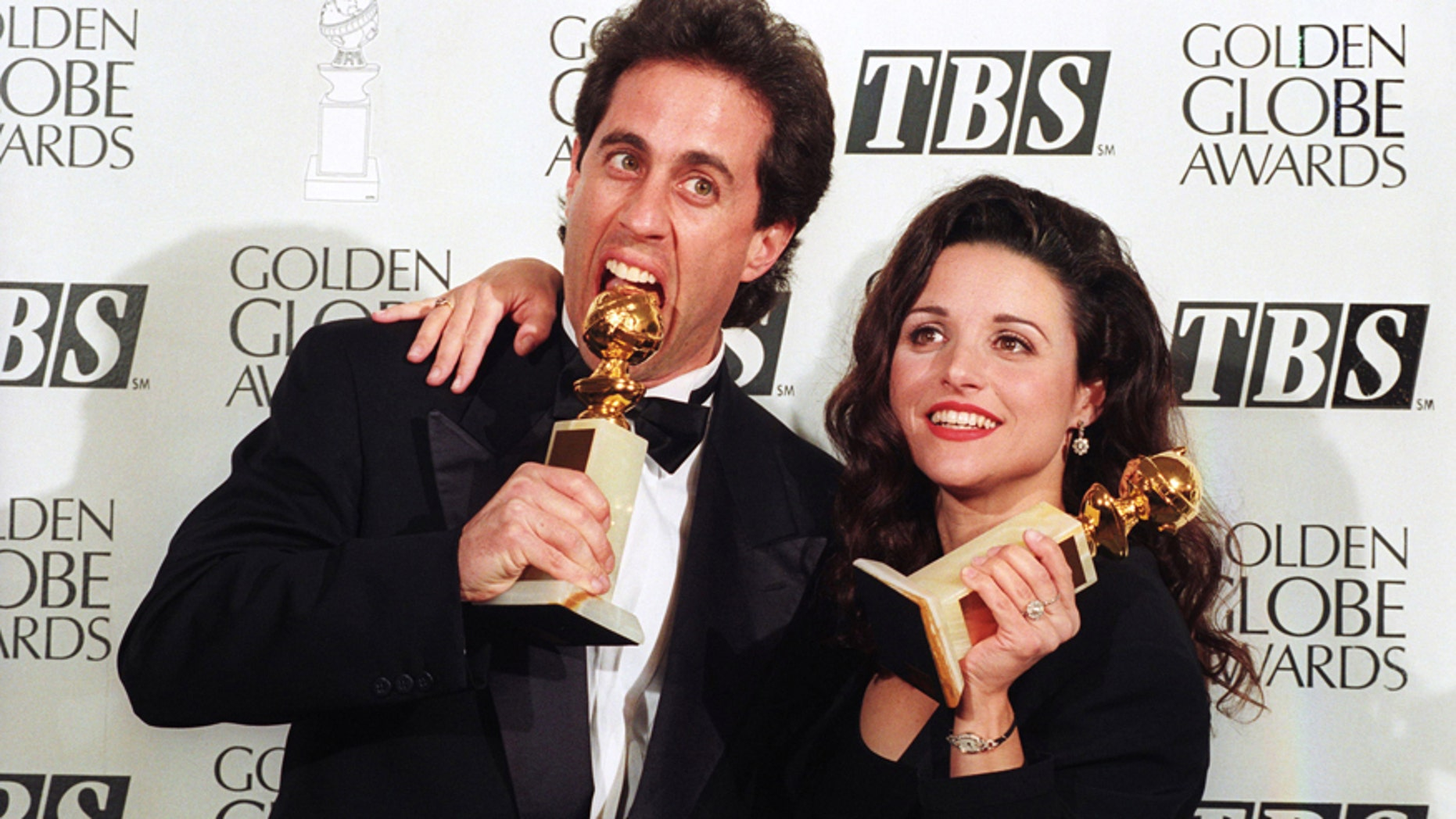 Jerry Seinfeld and Julia Louis-Dreyfus show their Golden Globe awards January 22, 1994.