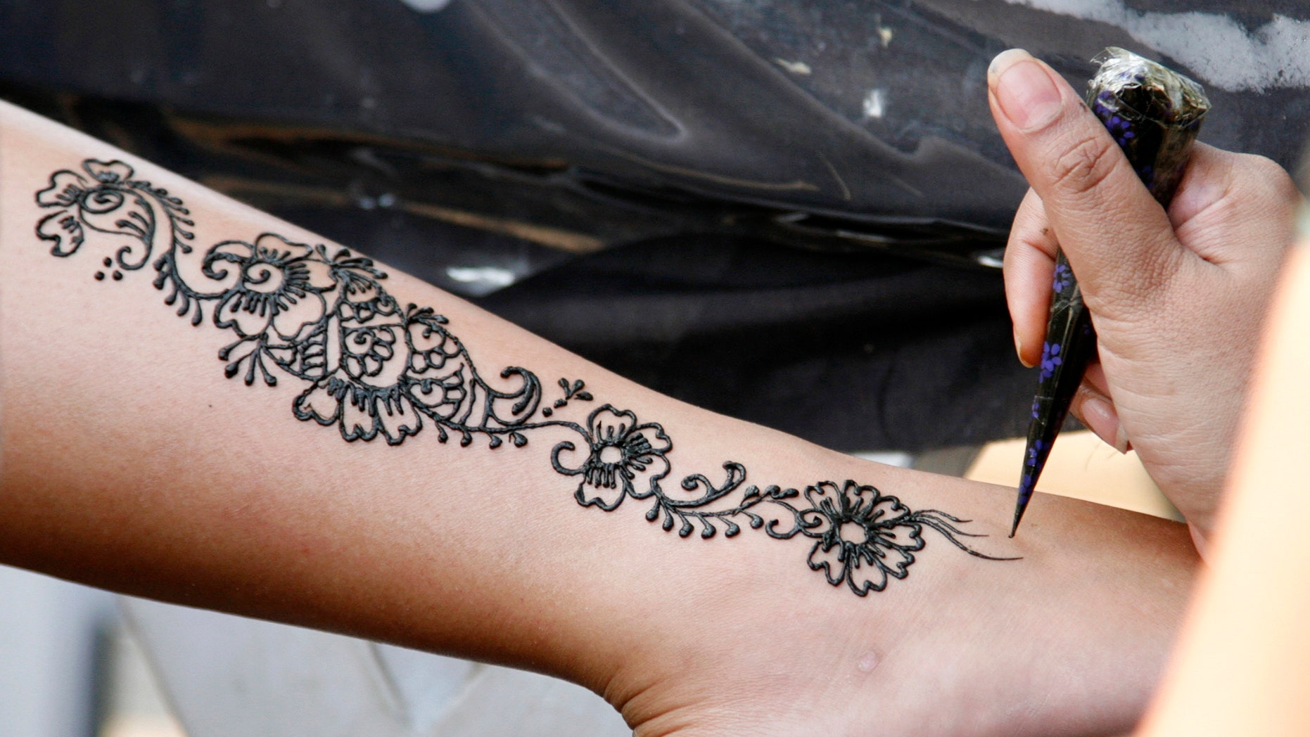 An artist demonstrates her skills with henna at a showcase of tattoo art during the Singapore Art Show 2007. (REUTERS/Rob Dawson)
