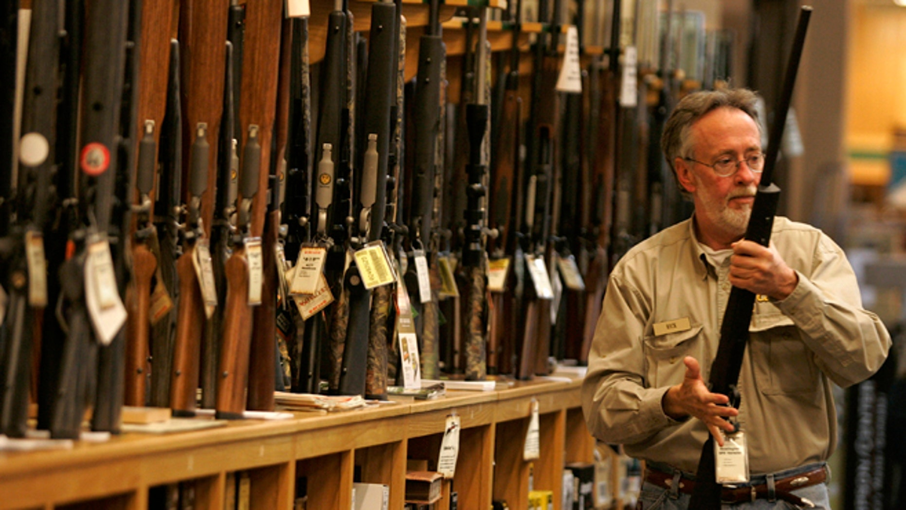 A salesman takes a rifle off the rack to show a customer at the Cabela's store in Fort Worth, Texas.