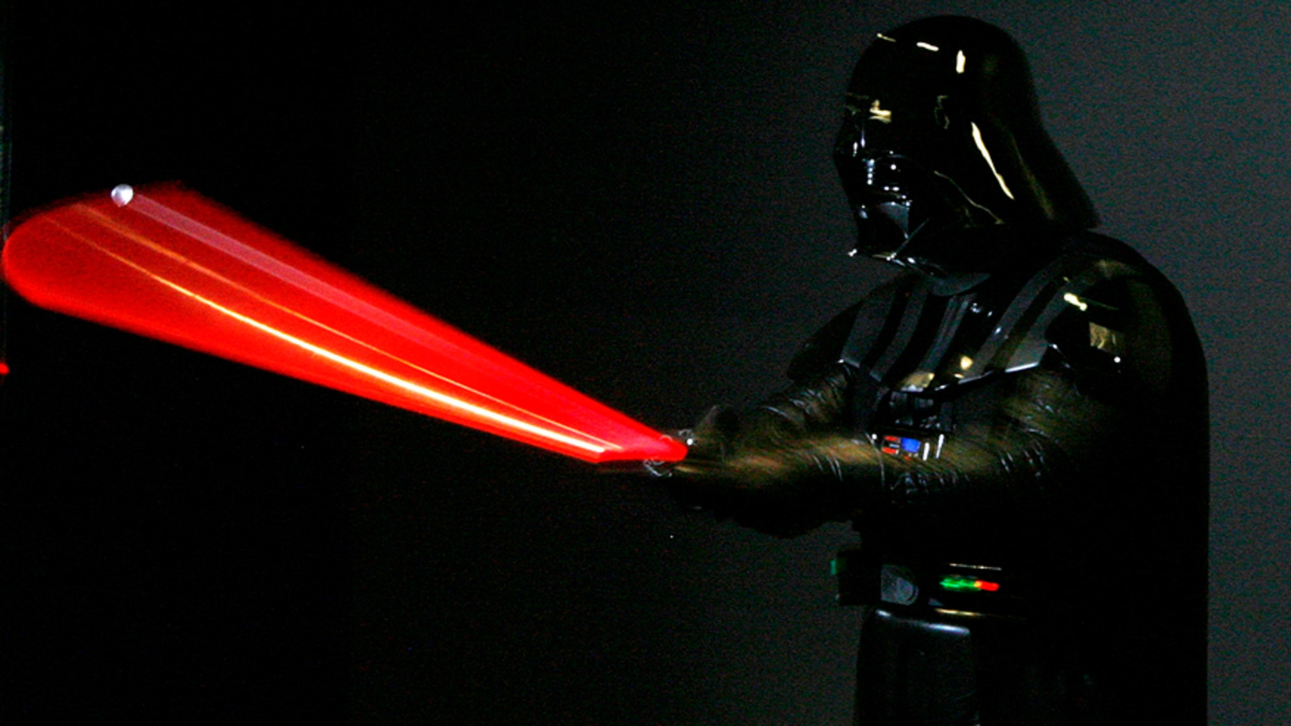 """A man dressed as Star Wars character Darth Vader poses for photographers at the """"Star Wars: Where Science Meets Imagination"""" exhibition at the Powerhouse Museum in Sydney December 3, 2008."""