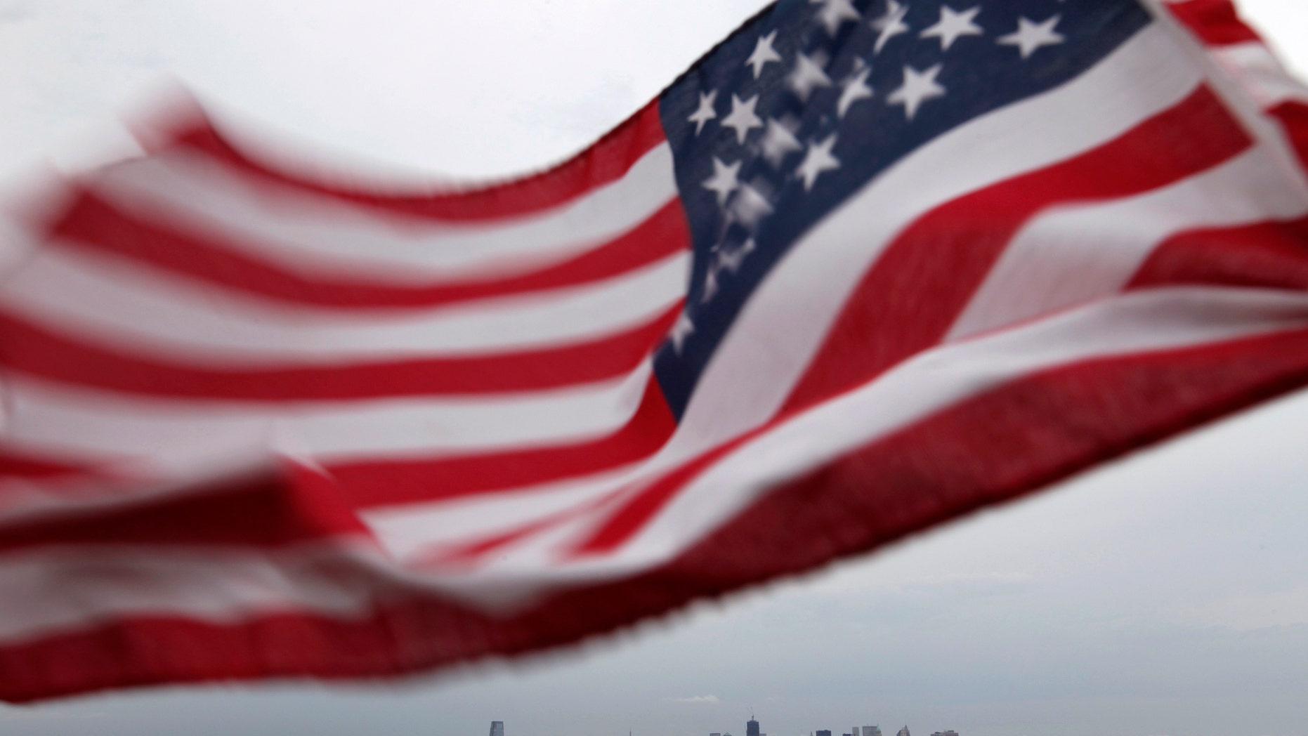 A U.S. flag flutters over top of the skyline of New York (R) and Jersey City (L), as seen from Bayonne, New Jersey, August 6, 2011. New York will mark the 10th anniversary of the attack on the World Trade Center with ceremonies on September 11. REUTERS/Gary Hershorn (UNITED STATES - Tags: CITYSCAPE DISASTER IMAGES OF THE DAY)
