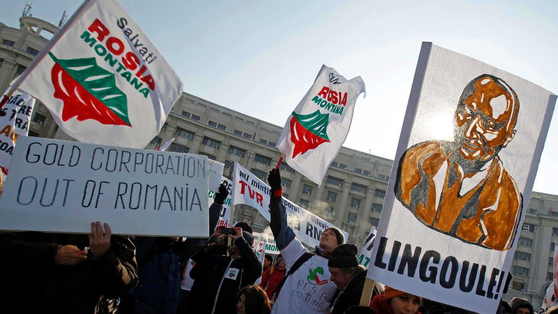 """January 28, 2012 - FILE photo of demonstrators waving flags that read """"Save Rosia Montana"""" and a banner depicting a gold figurine of Romania's President Traian Basescu, an open supporter of the gold mine project, during a protest in front of the Parliament palace in central Bucharest.  Hundreds of Romanians protested against a plan to set up Europe's biggest open-cast gold mine in the western Romanian town of Rosia Montana."""
