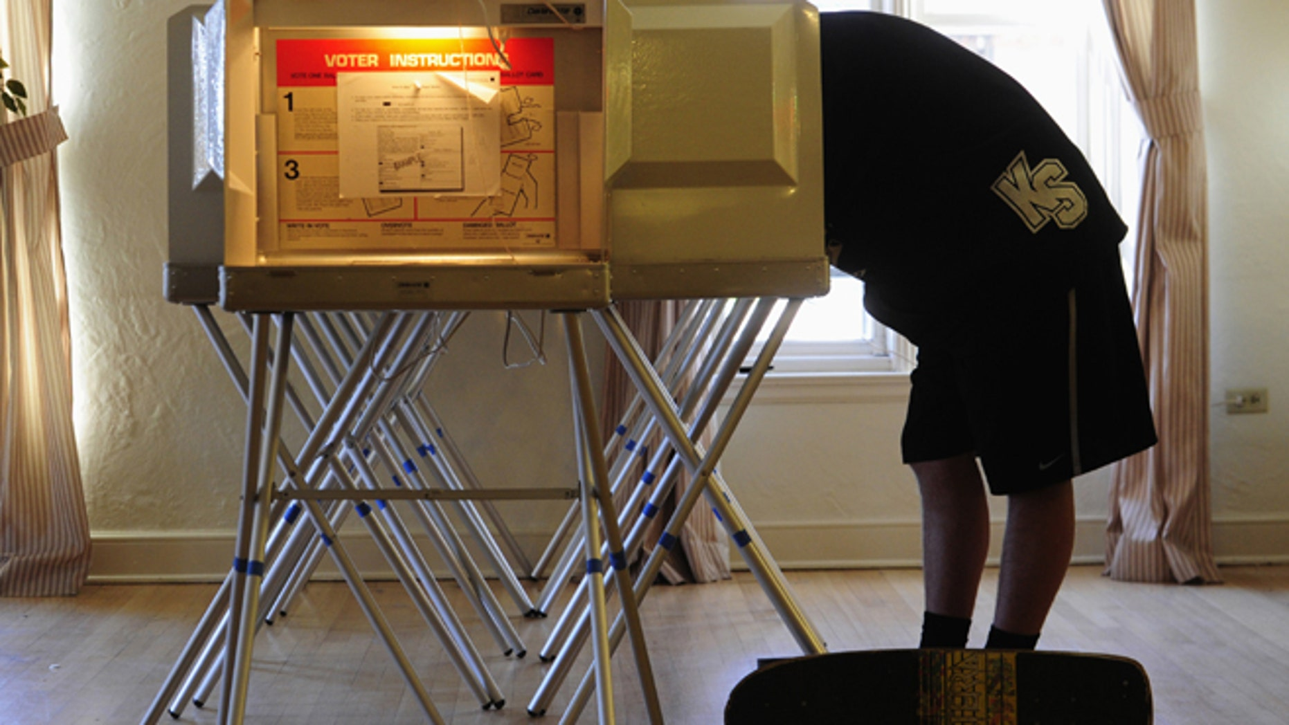 A college freshman leans into the voting booth while filling up his ballot. (REUTERS)