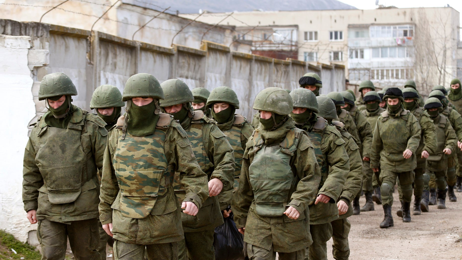 March 14, 2014 - Armed men, believed to be Russian servicemen, walk outside a Ukrainian military base in Perevalnoye, near the Crimean city of Simferopol. A Russian warship unloaded trucks, troops and at least one armored personnel carrier at a bay near Sevastopol in Crimea on Friday morning, as Moscow continued to build up its forces on the Ukrainian peninsula.  REUTERS