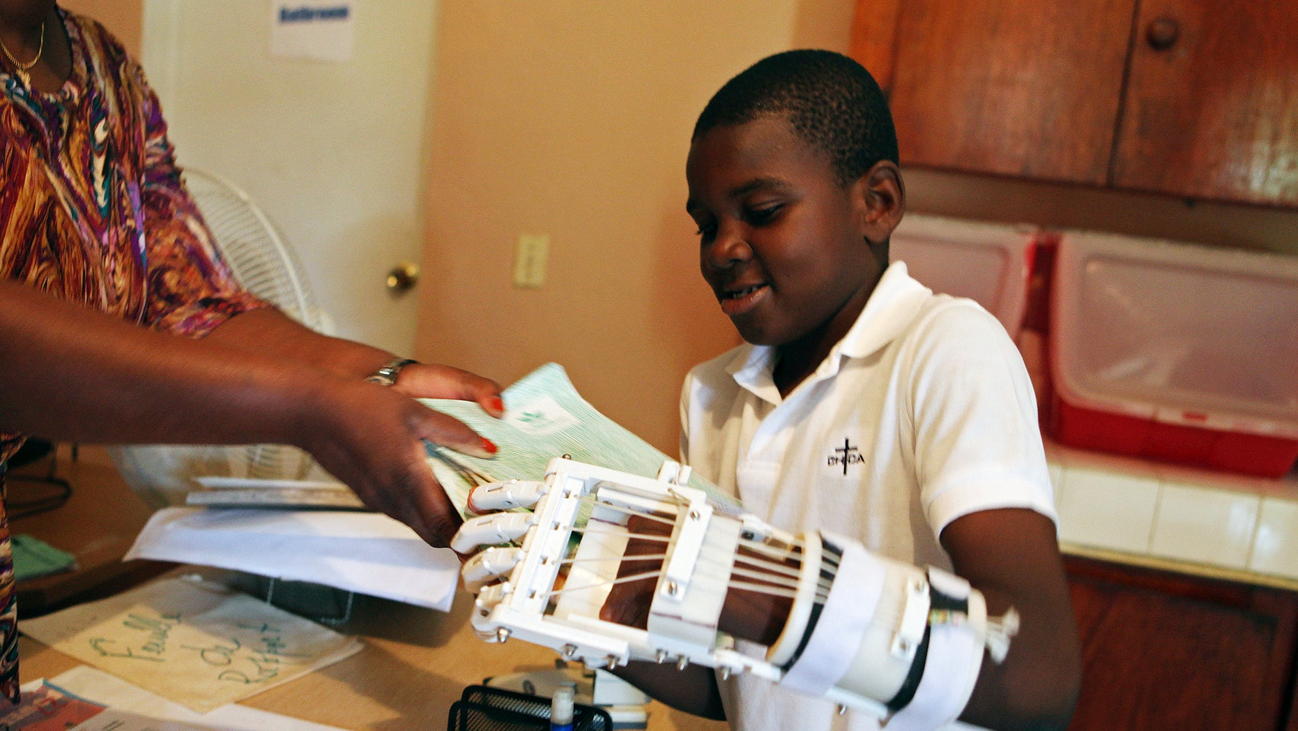 Handicapped Haitian boy Stevenson Joseph learns to use a 3D-printed prosthetic hand at the orphanage where he lives in Santo, near Port-au-Prince, April 28, 2014. (REUTERS/Marie Arago)