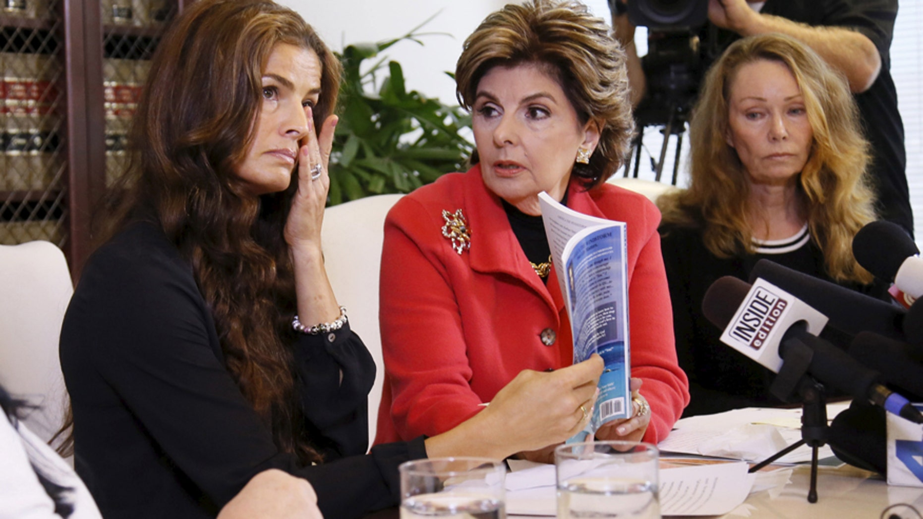 Former Mrs. America Lisa Christie (L), who alleges misconduct by Bill Cosby along with two others in the room, Sharon Van Ert (R) and Pamela Abeyta (not pictured), cries as she reads a paragraph from her book during a news conference with attorney Gloria Allred (C) at Allred's law office in Los Angeles, September 30, 2015.