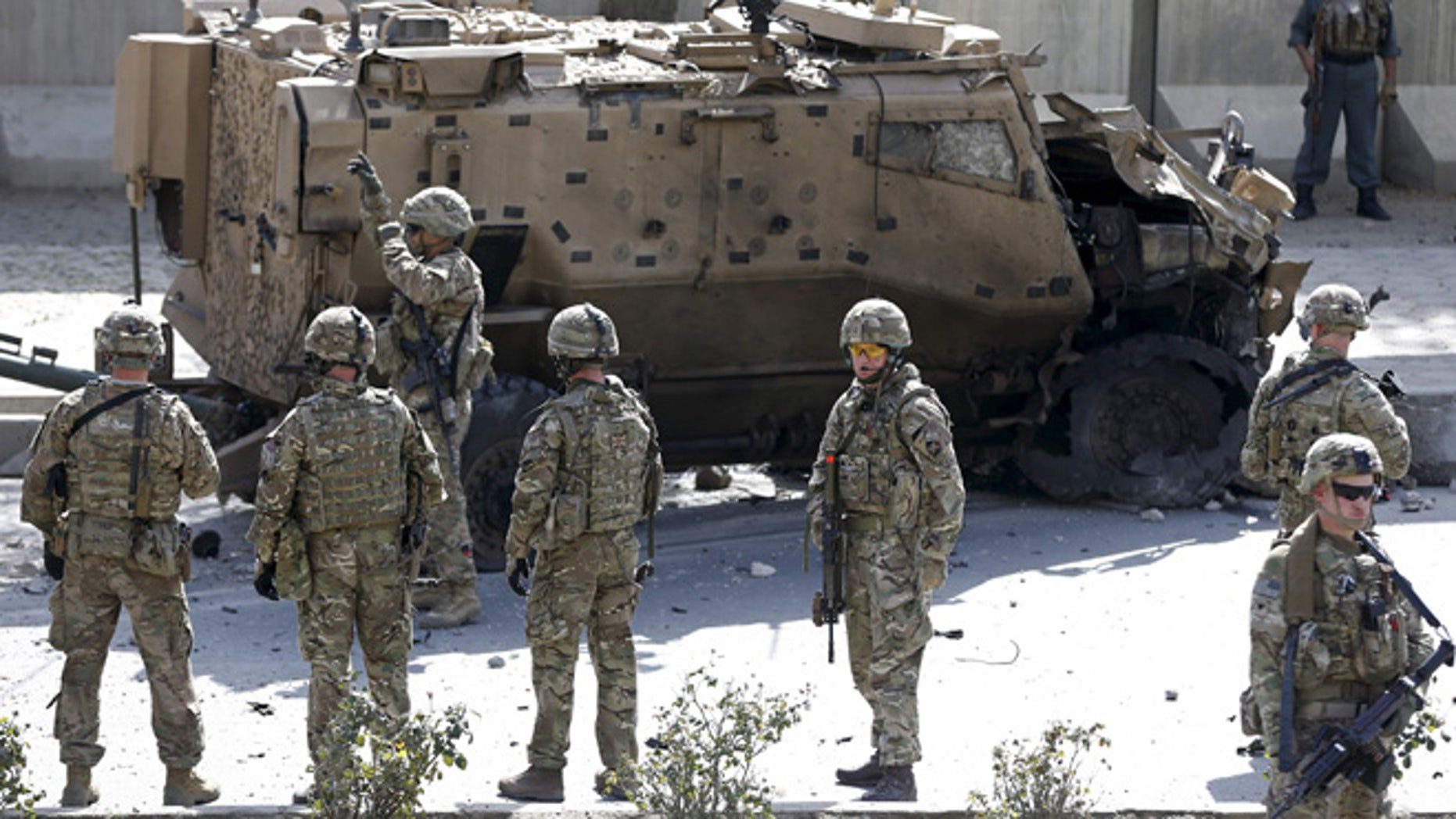 Oct. 11, 2015: NATO soldiers stand near a damaged NATO military vehicle at the site of a suicide car bomb blast in Kabul, Afghanistan.