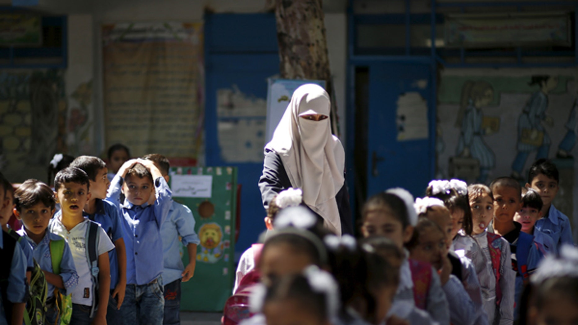 September 22, 2015: A veiled Palestinian teacher stands next to children as they queue at a United Nations Relief and Work Agency (UNRWA)-run school in Gaza. A recent investigation by the Center for Near East Policy Research found that many of the schools are using texts that are authored by the Palestinian Ministry of Education and its contents not fail to recognize the state of Israel.
