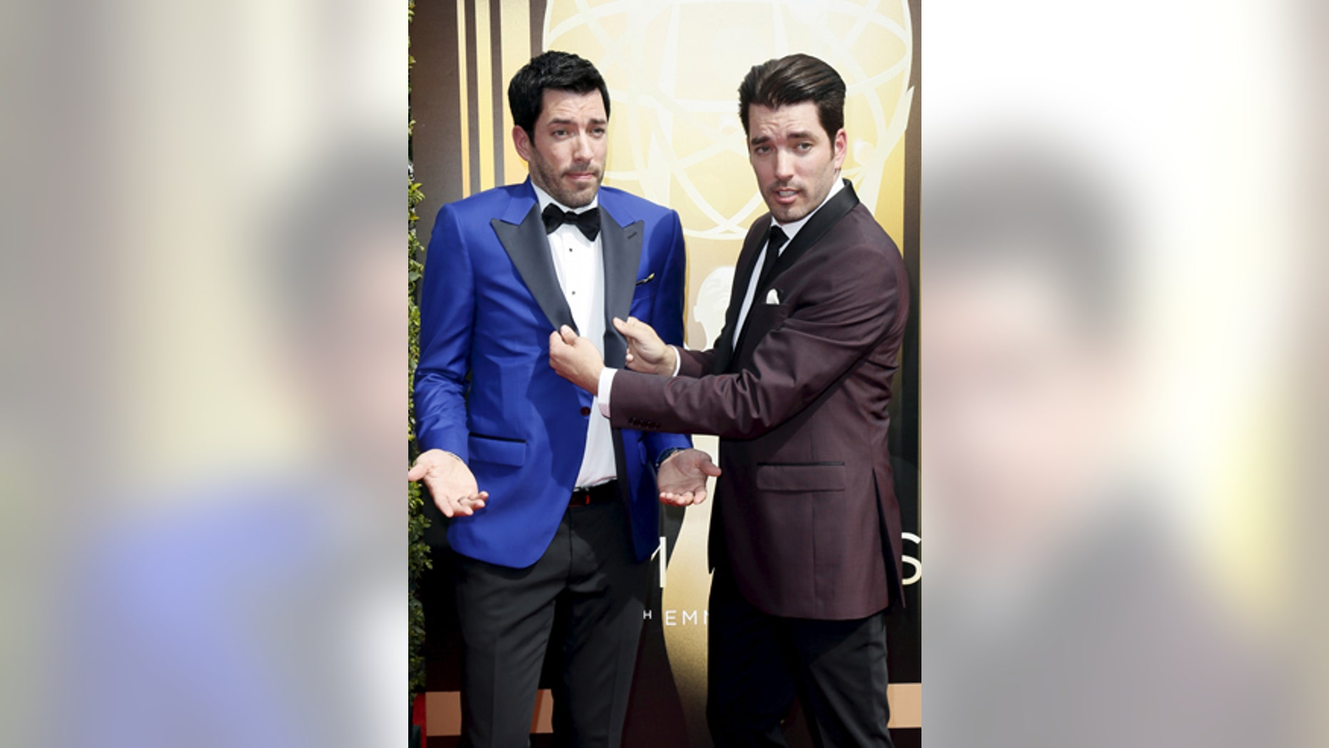Television personalities Drew Scott (L) and twin brother Jonathan Scott pose at the 2015 Creative Arts Emmy Awards in Los Angeles, California September 12, 2015.