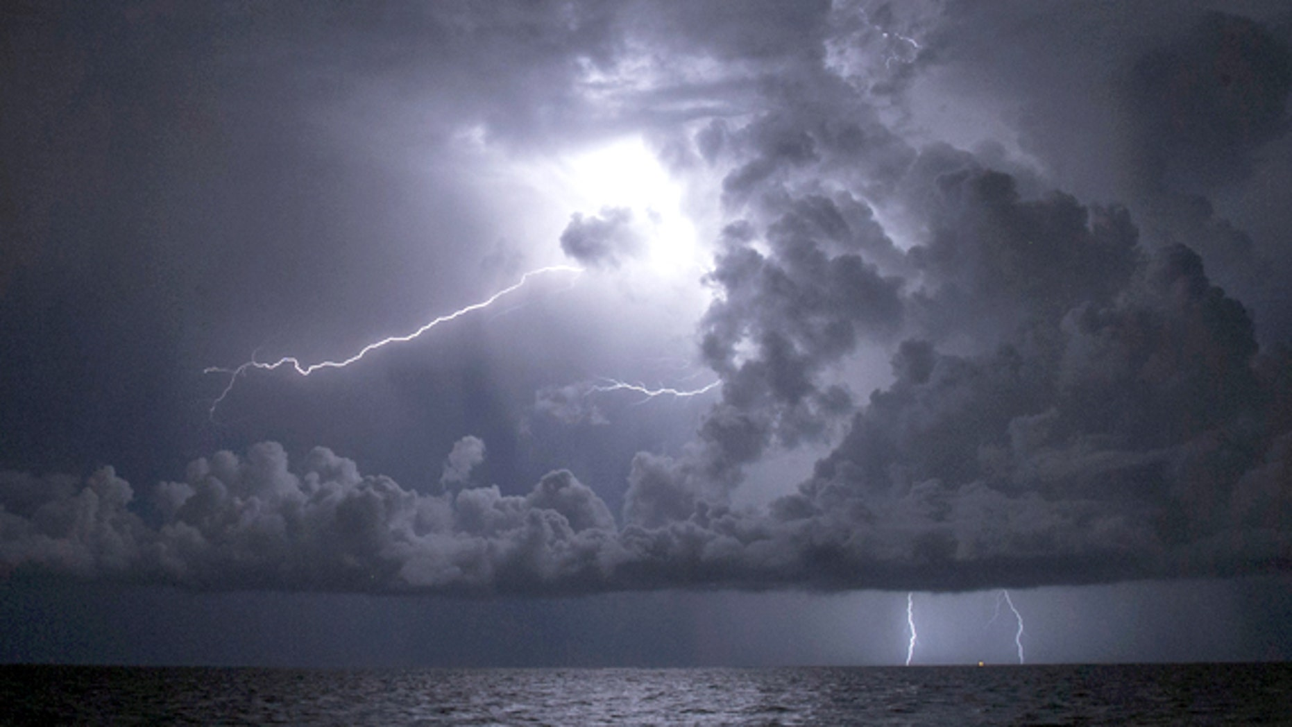 A lightning storm is pictured over the sea near the popular tourist destination of Cancun August 13, 2013.