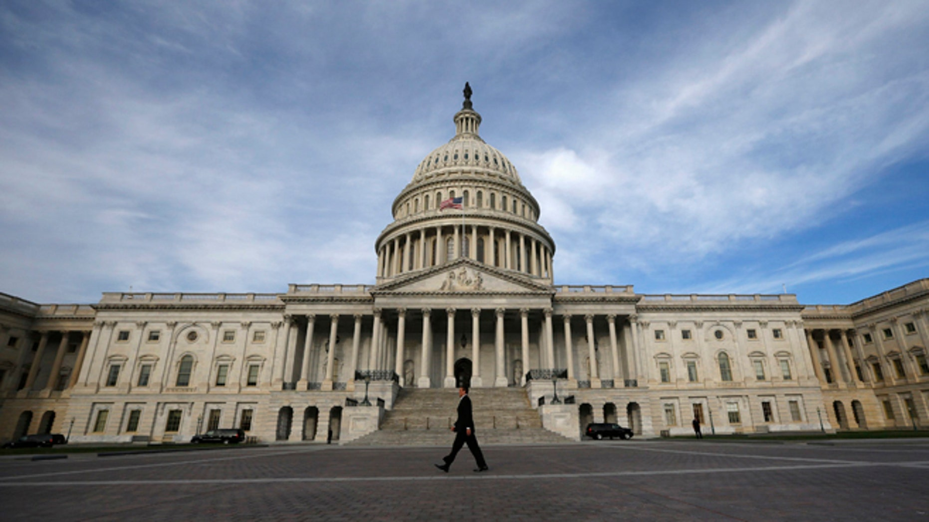 A lone worker passes by the U.S. Capitol building in Washington, October 8, 2013.