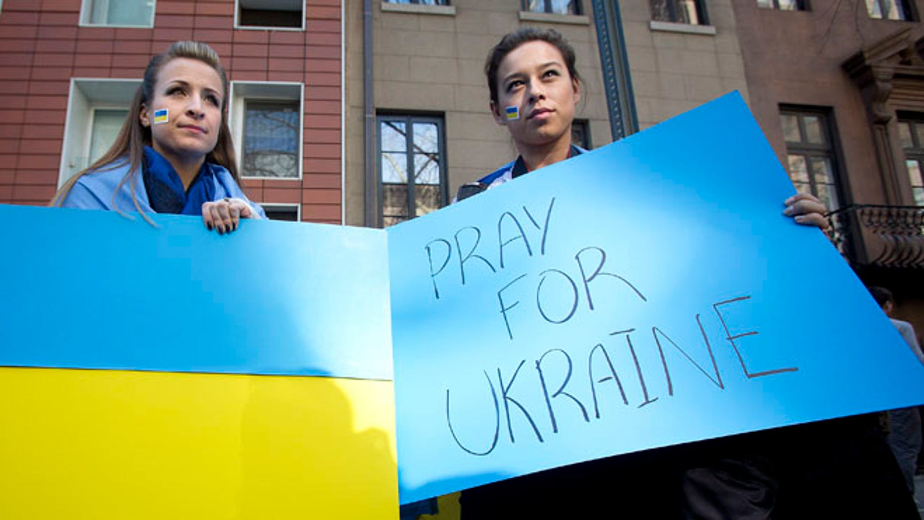 Feb. 23, 2014: A woman carries a Ukraine flag and another a sign of support  in New York City.