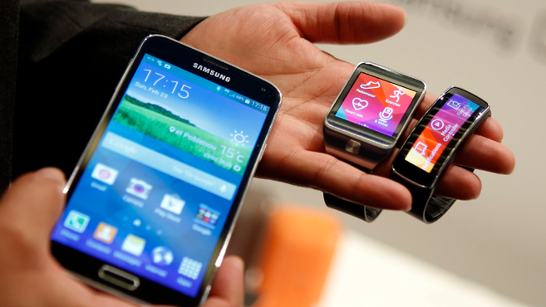 New Samsung Galaxy S5 smartphone (L), Gear 2 smartwatch (C) and Gear Fit fitness band are displayed at the Mobile World Congress in Barcelona.